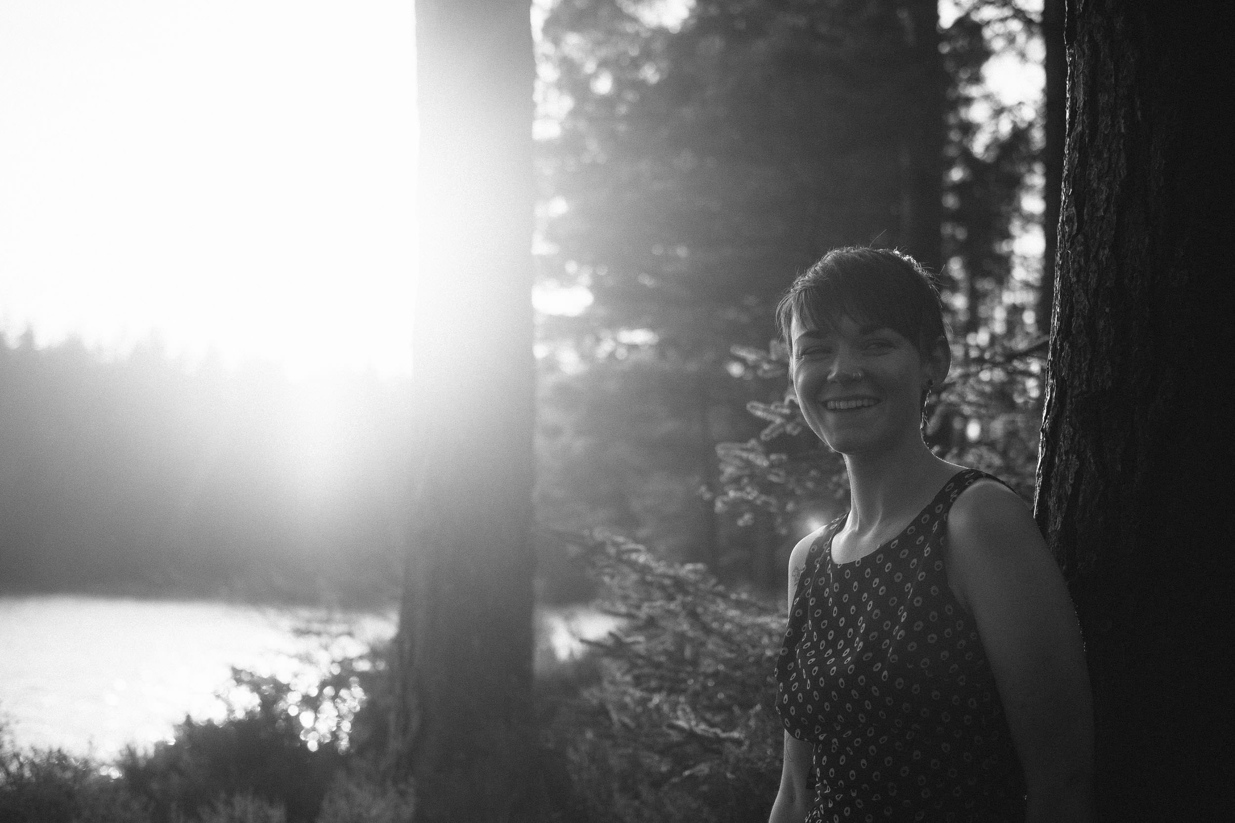 A black and white photo of girl smiling in a forest in strong sunshine