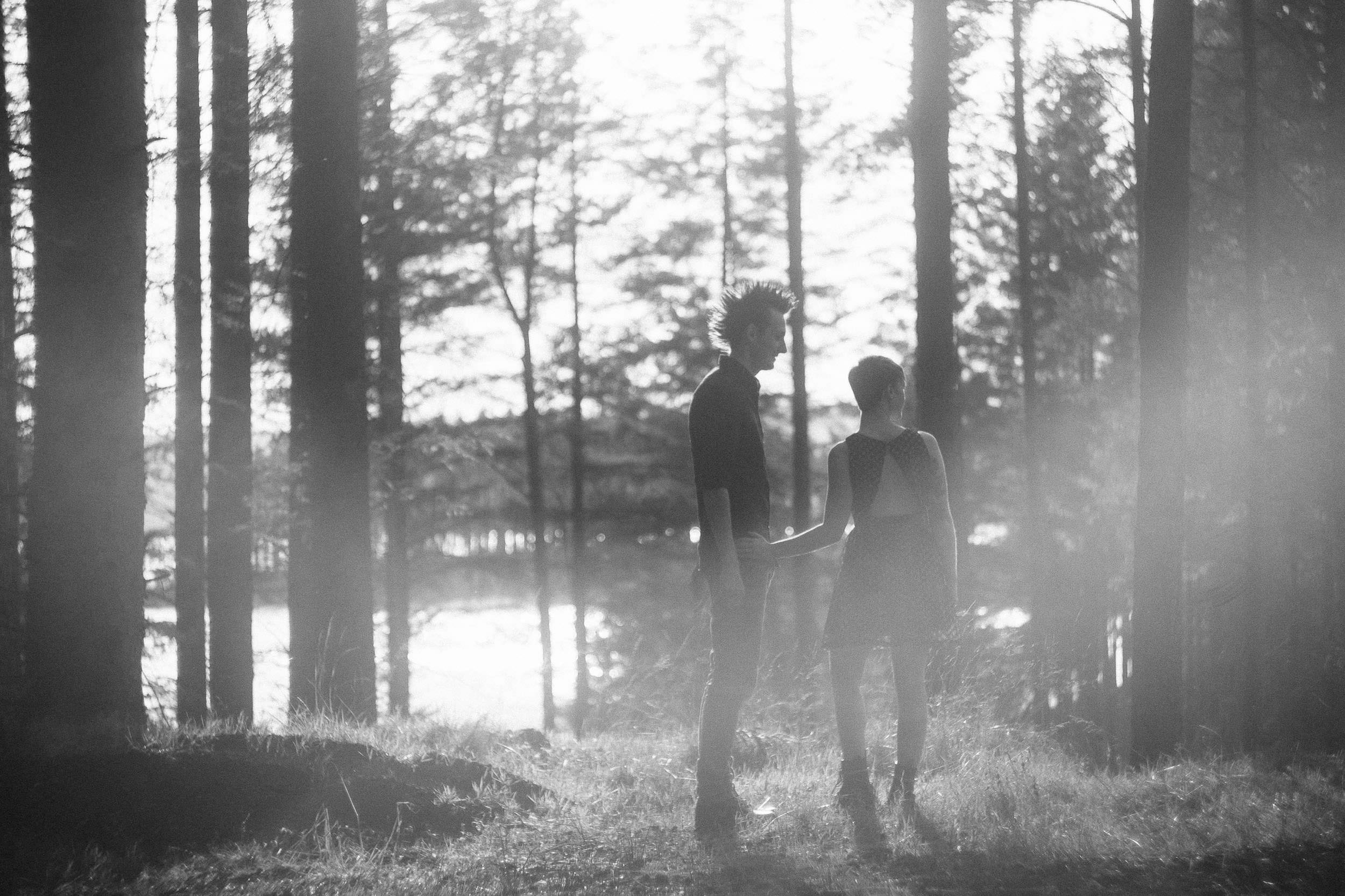 A dreamy black and white photo of sun bursting through trees and hitting engaged couple