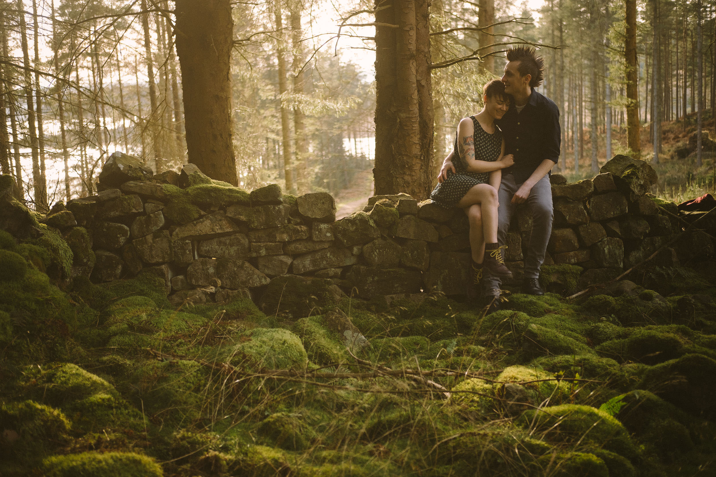 Engaged couple sit on a ruined wall in a forest