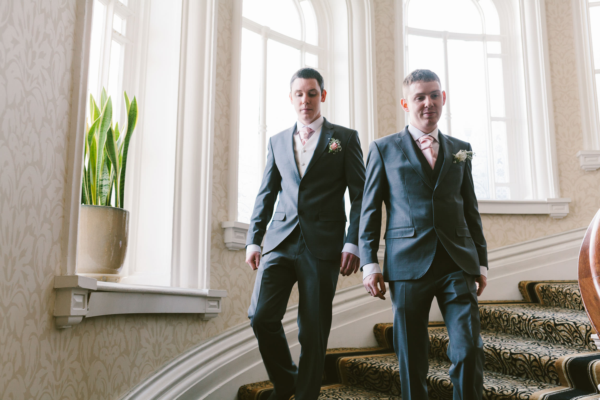 Groom and best man walk down grand staircase in Grand Hotel Newcastle