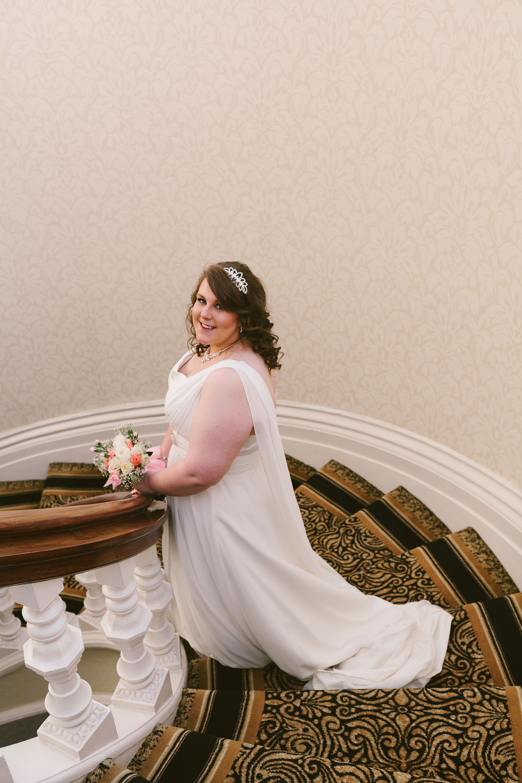 A portrait of the bride standing on the staircase steps of the Grand Hotel