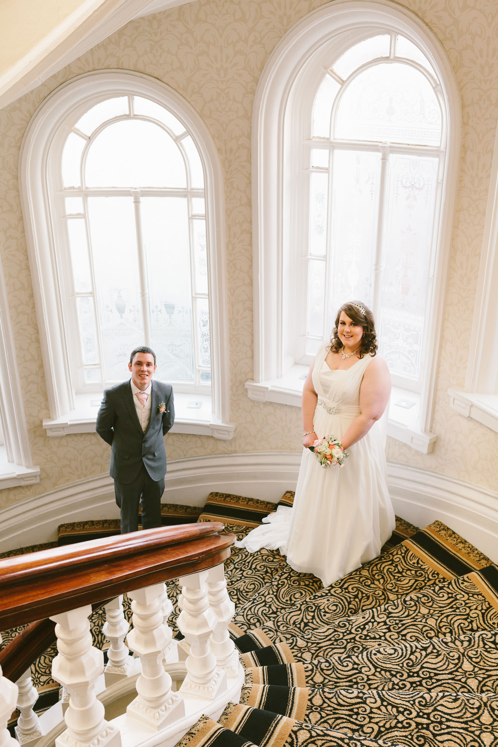 Bride and groom pose in front of tall windows on the staircase of the Grand Hotel
