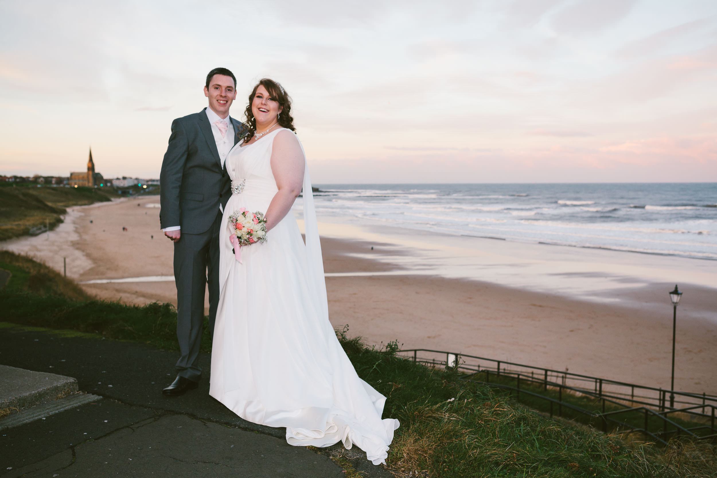 Bride and groom pose above Tynemouth Longsands at sunset