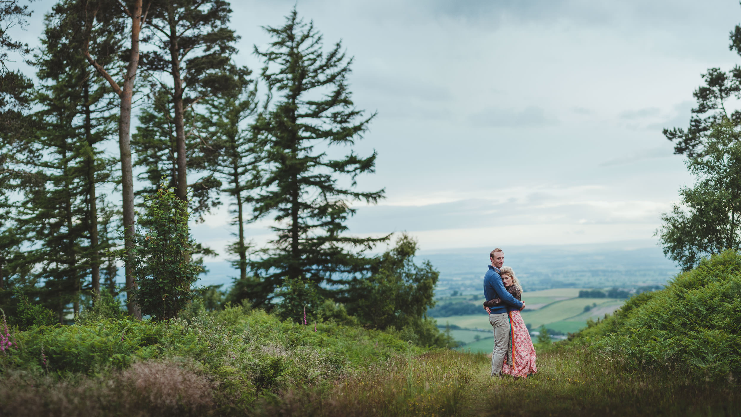 Couple cuddle on path high in hills with trees either side