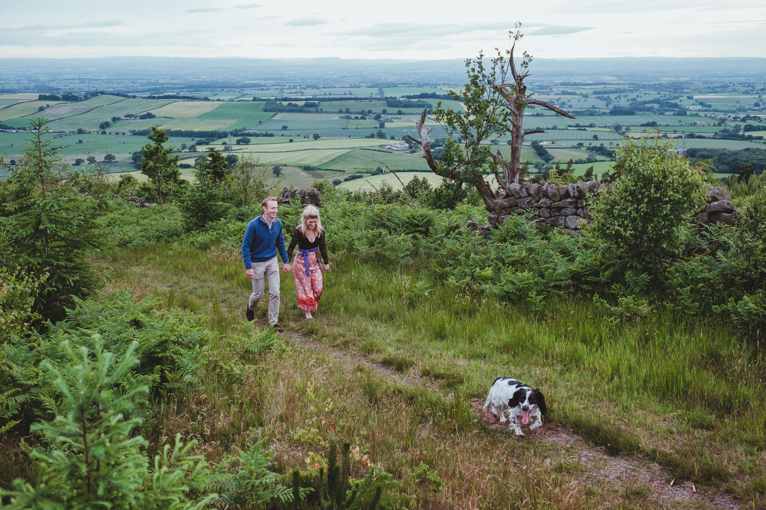 A couple walk hand in hand up a country path overlooking the Yorkshire countryside