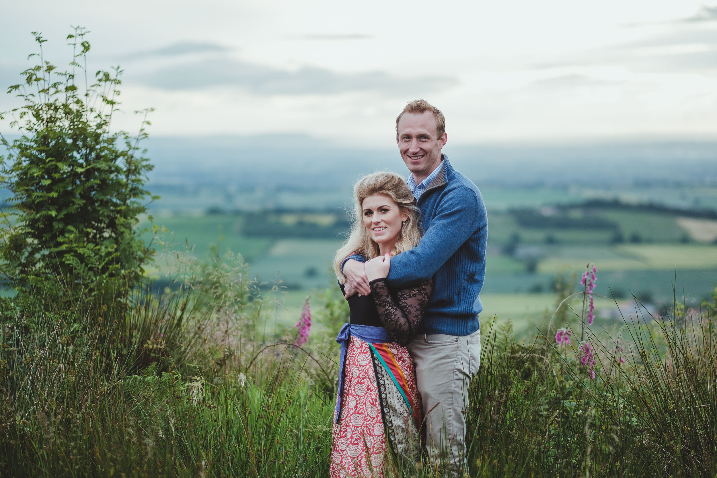 A couple cuddle for the camera with stunning views of Yorkshire behind