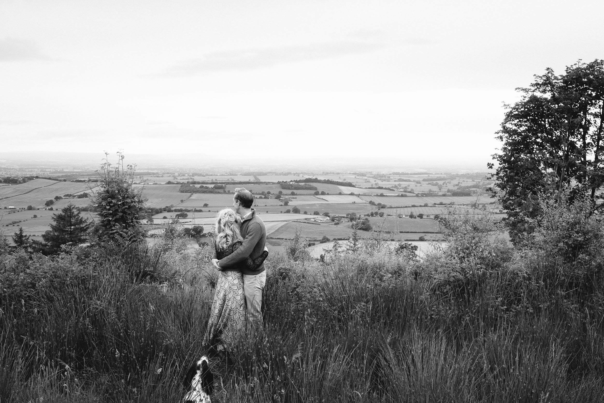A black and white photo of a couple holding each other looking out over the Yorkshire countryside