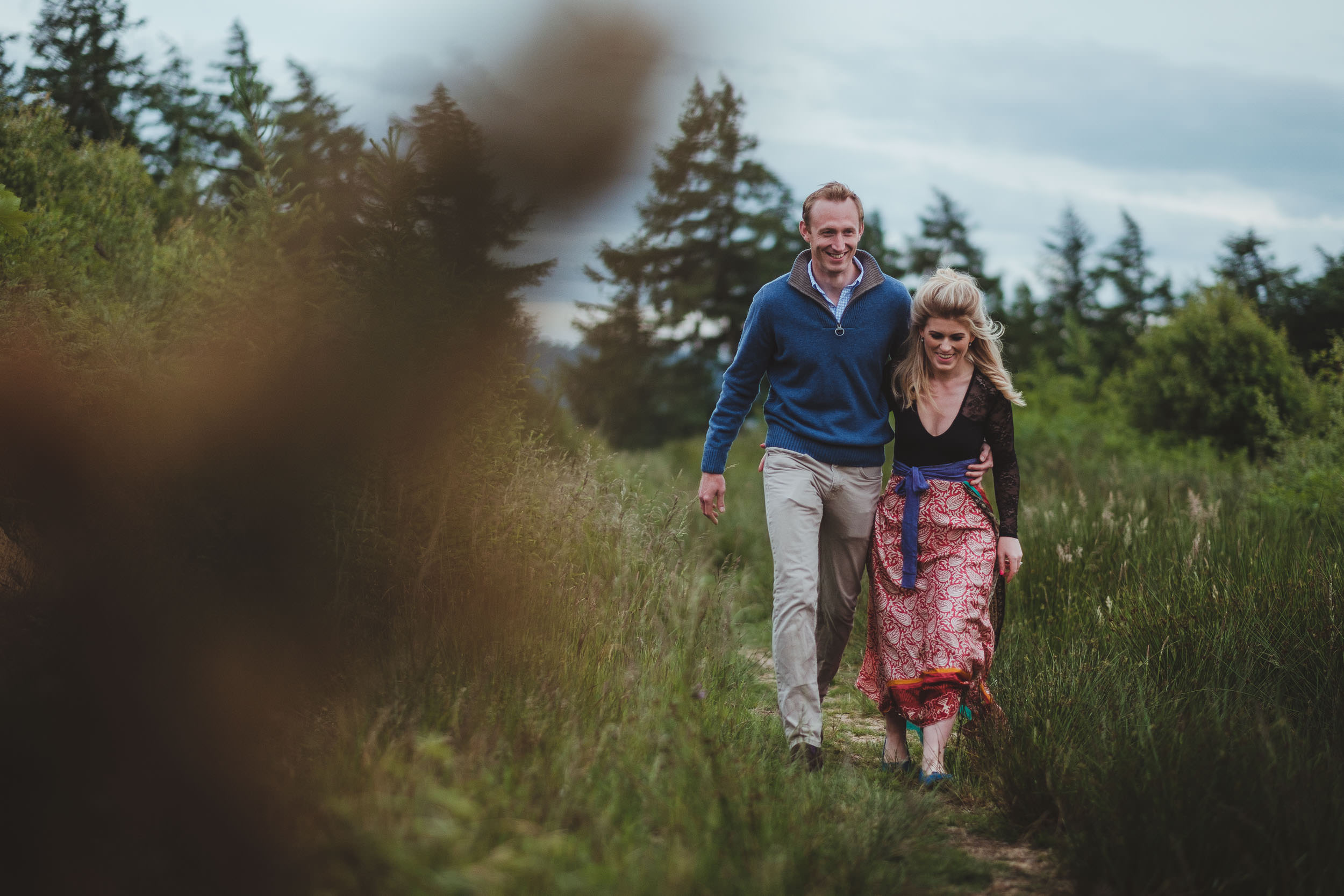 A couple walk arm in arm down a country path in Yorkshire