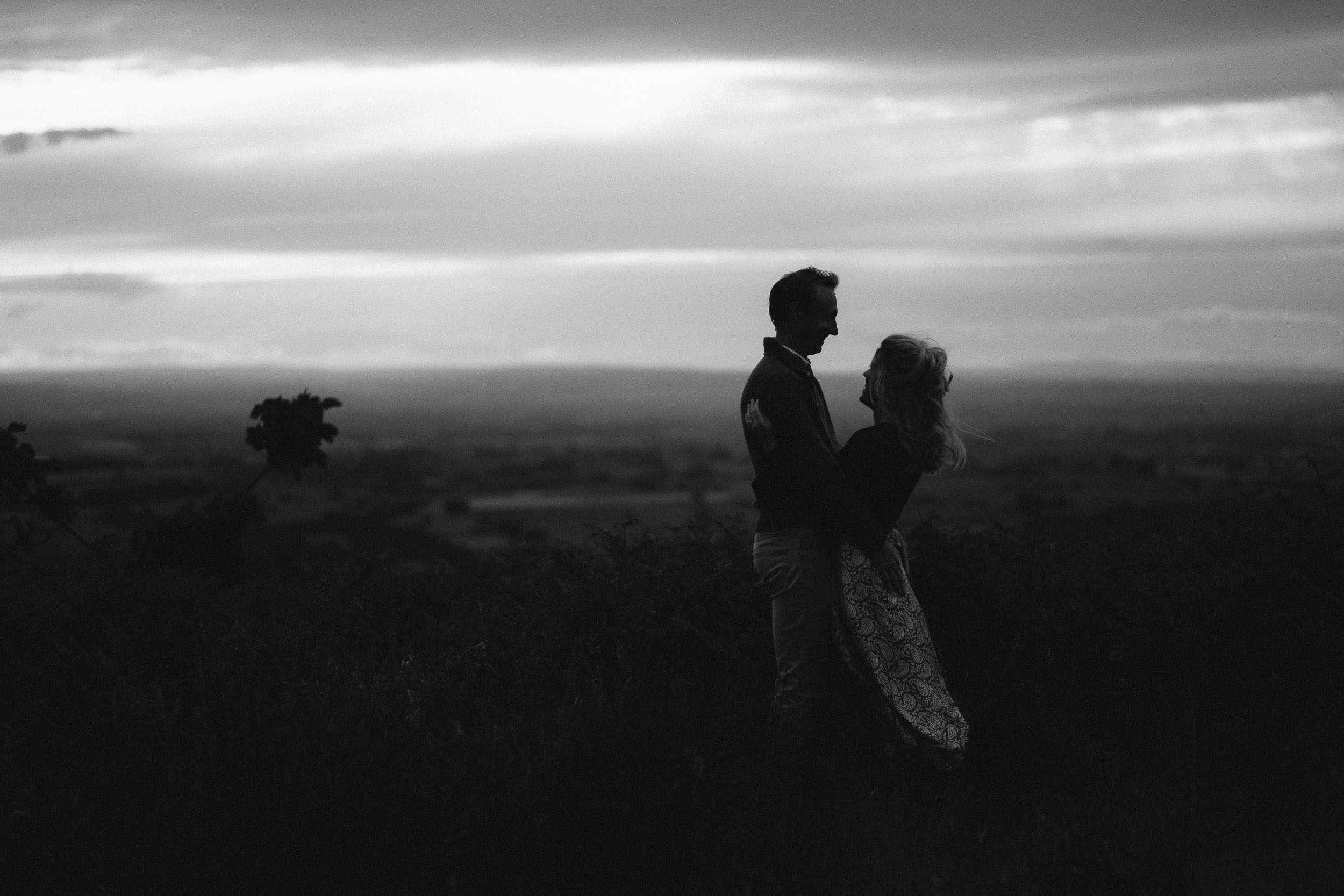 A black and white photo of an engaged couple holding each other with a dramatic sky behind them