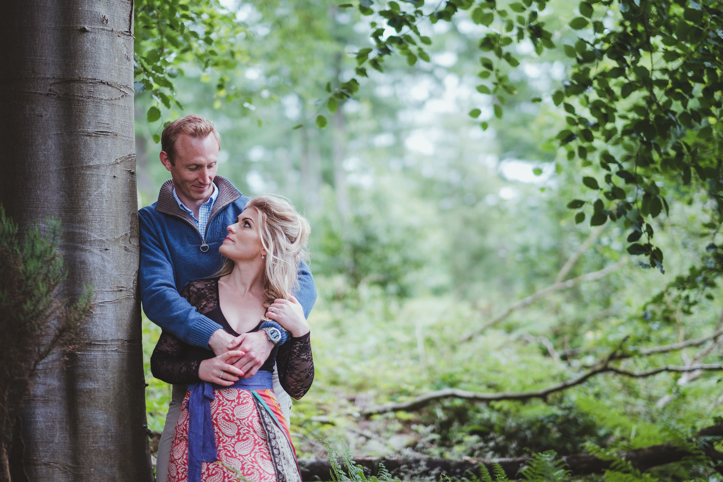 An engaged couple looking into each other's eyes while leaning against a tree