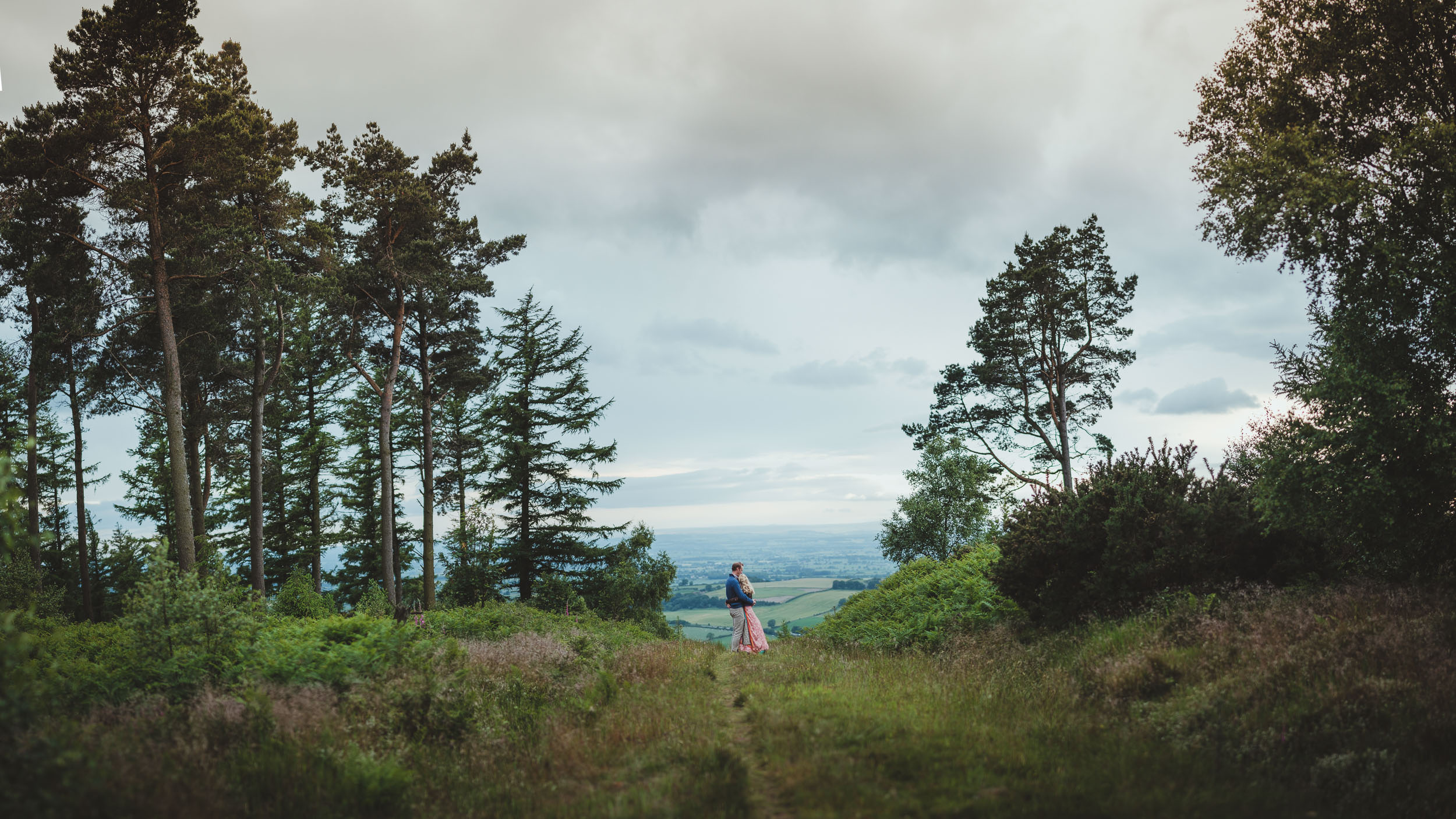A wide panorama of a country path high in the Yorkshire hills with an engaged couple cuddling