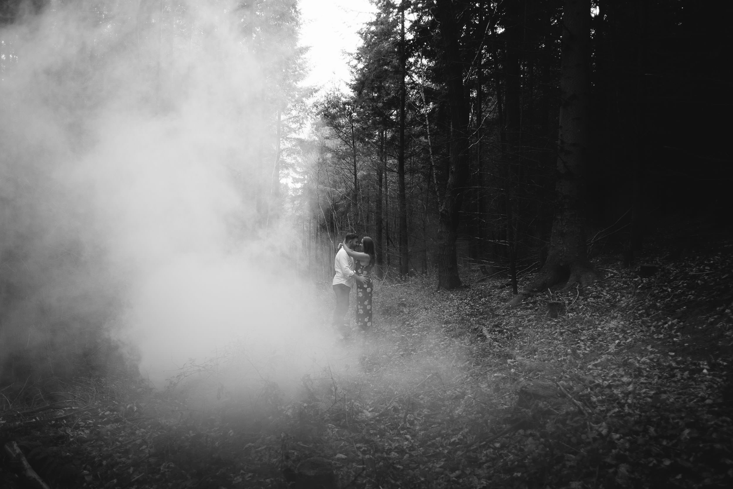 A black and white photo of a couple embracing in a wood while smoke curls around them