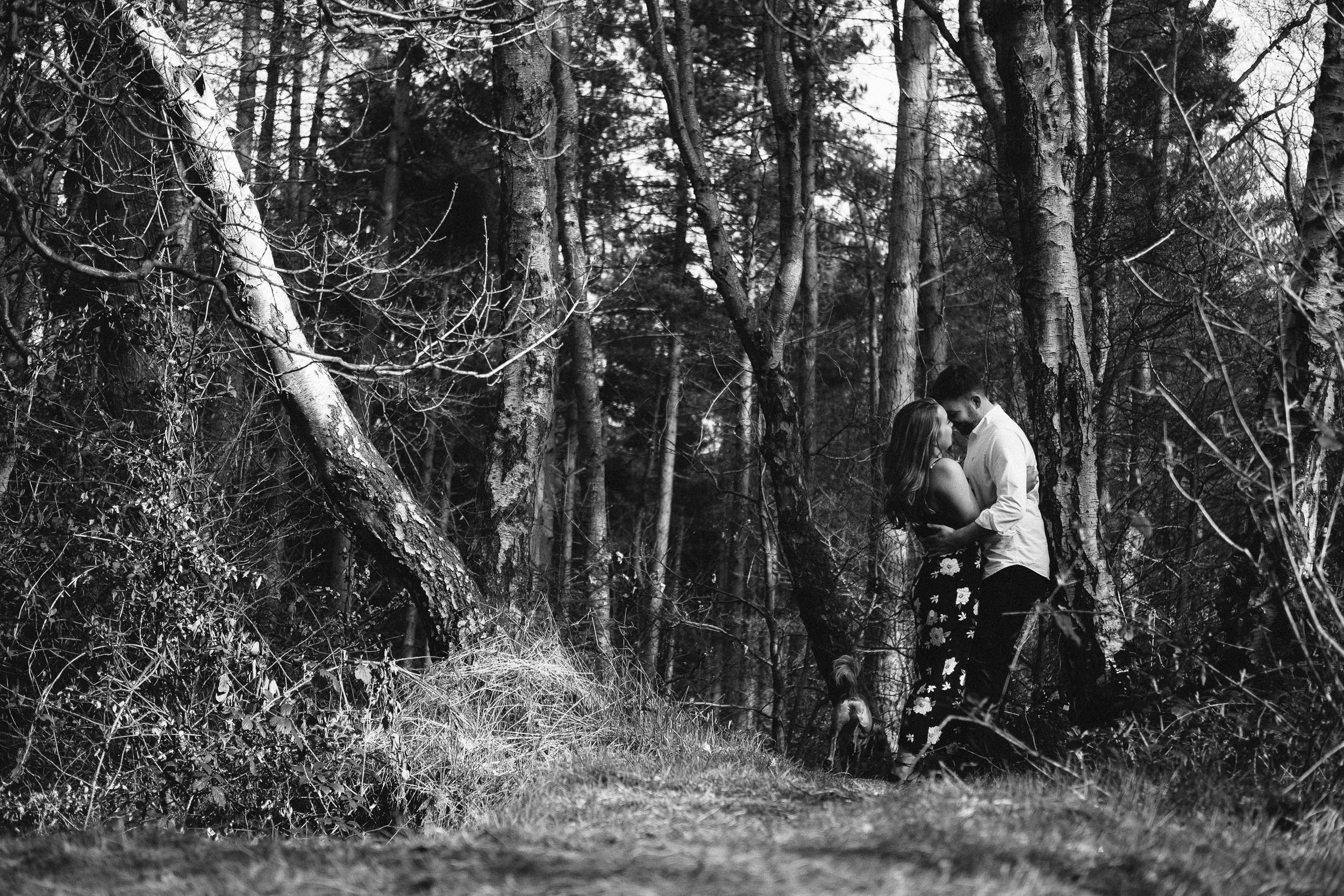 A dramatic black and white photo of a couple embracing in wild woodland