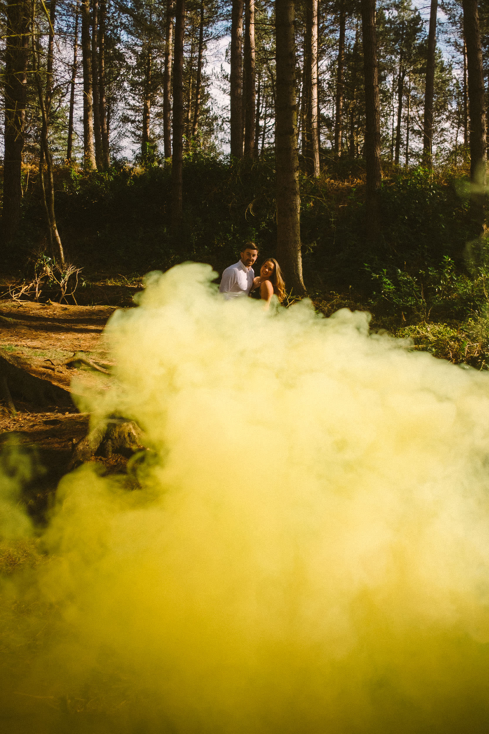 A couple are completely engulfed in smoke during their engagement shoot in the woods