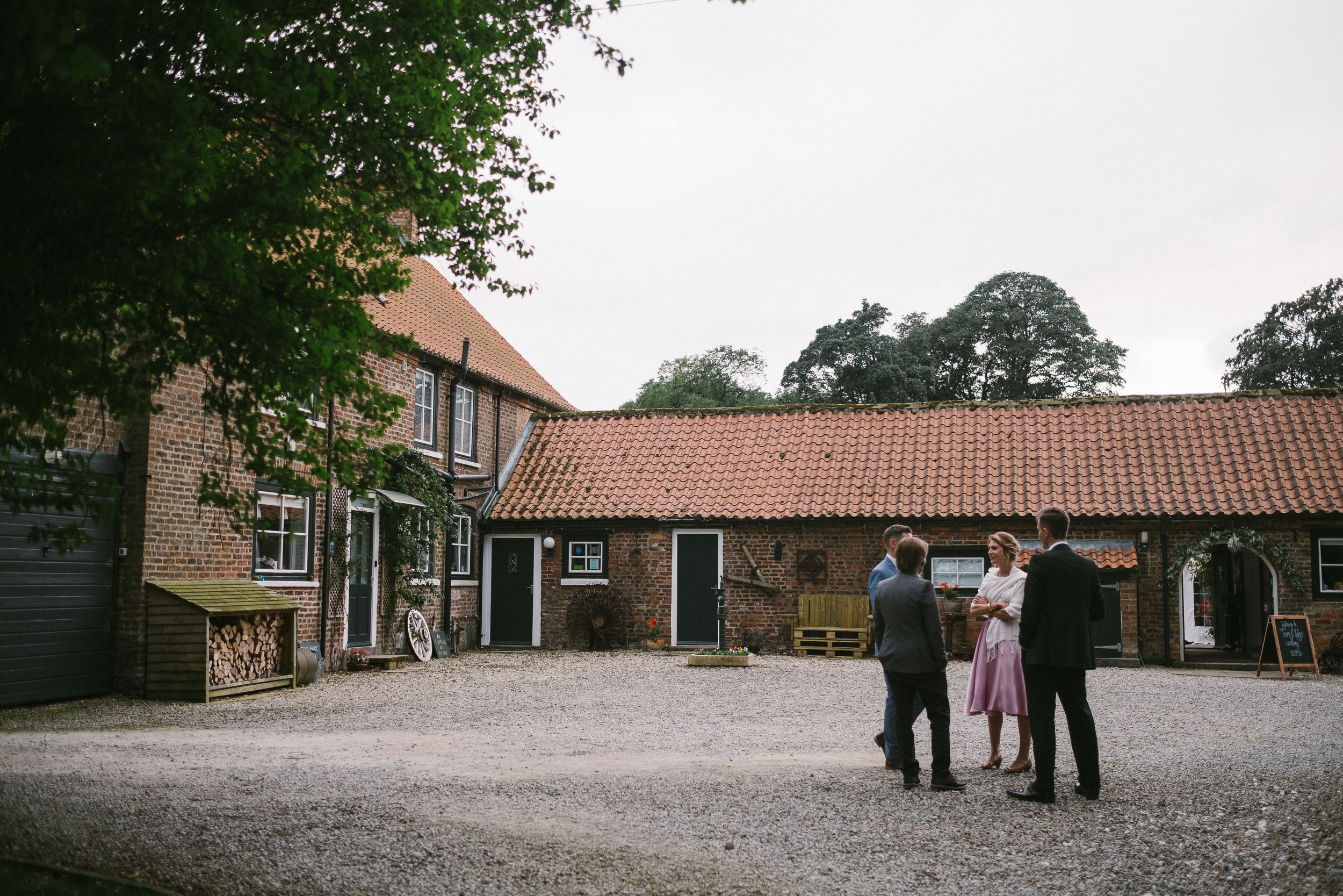 Wedding guests chatting at the main entrance to Dale Farm
