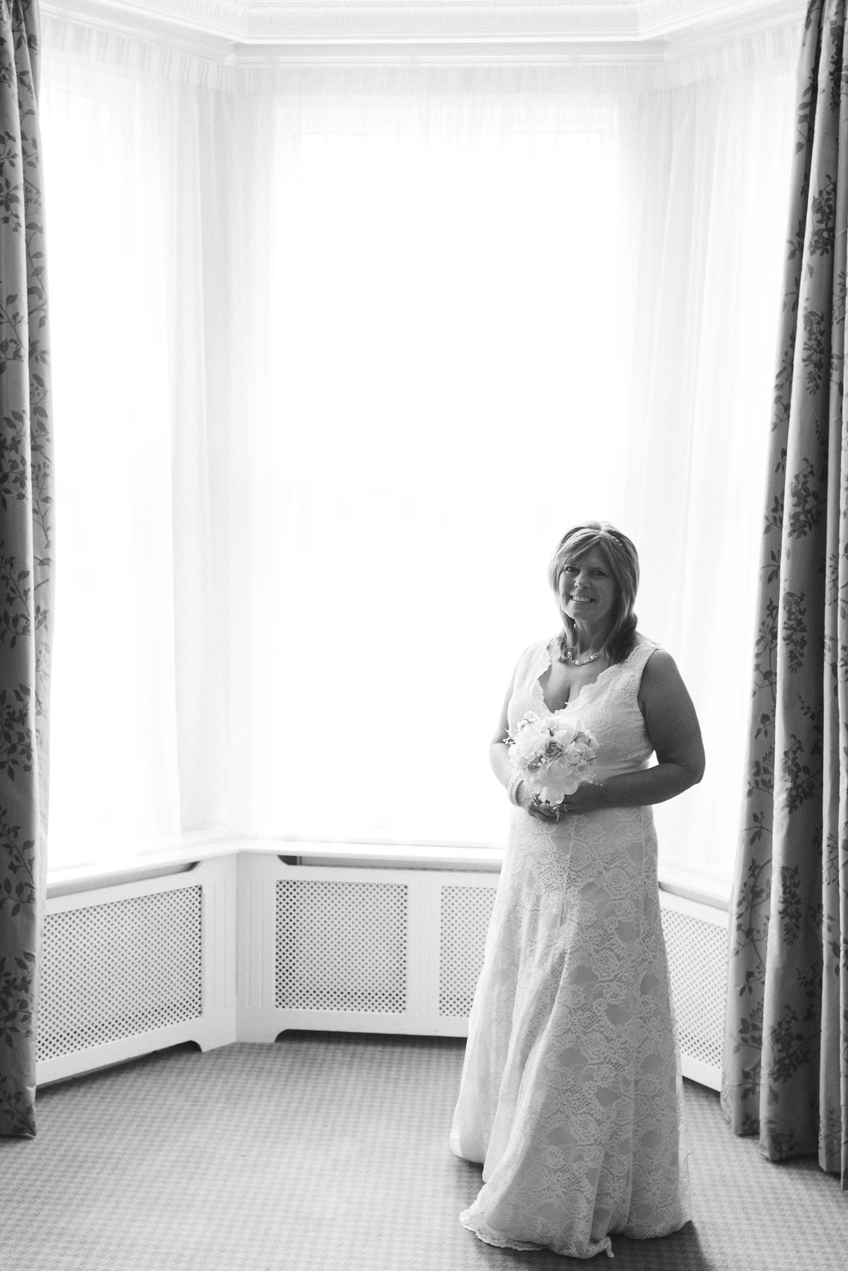 A black and white photo of the bride standing in front of a tall window