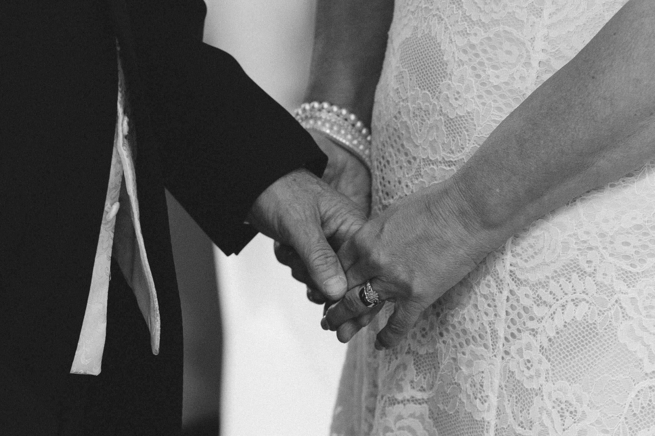 A black and white photo of the bride and groom holding hands during the wedding ceremony