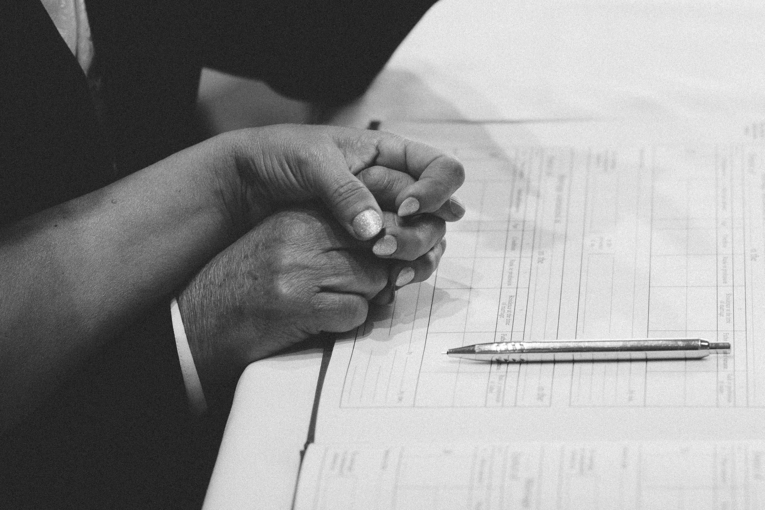 A black and white photo of the bride and groom holding hands after signing the marriage register