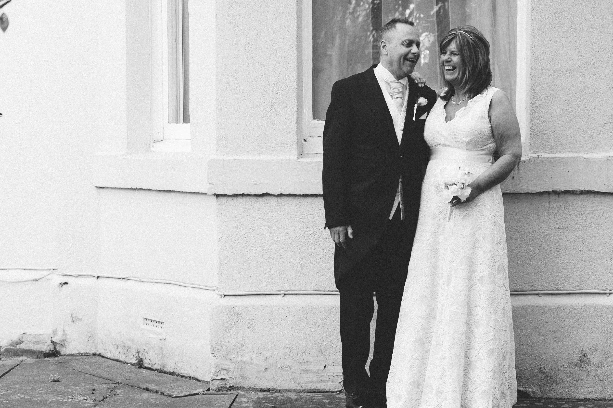 A black and white photo of the bride and groom laughing outside the Caledonian hotel Newcastle