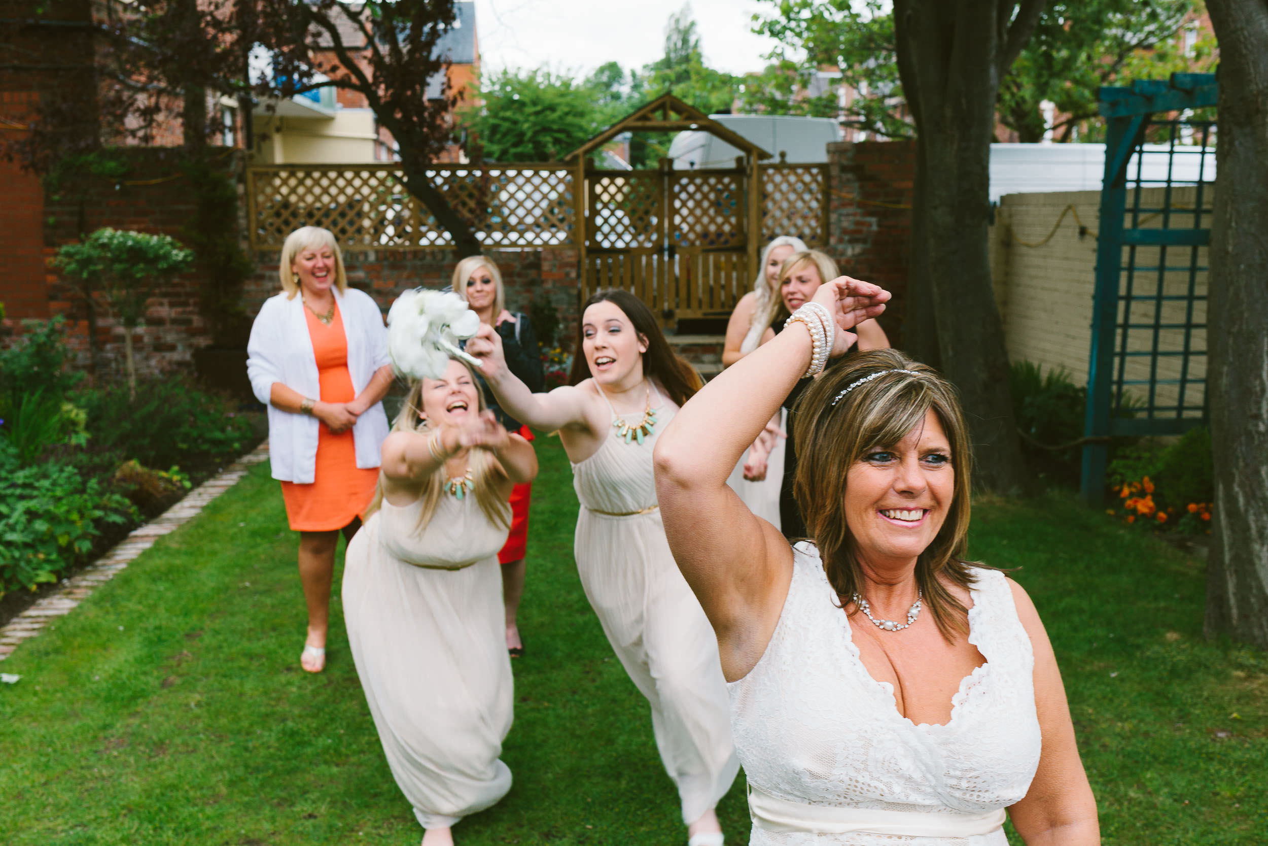 The bride throws the bouquet and the bridesmaids leap to catch it