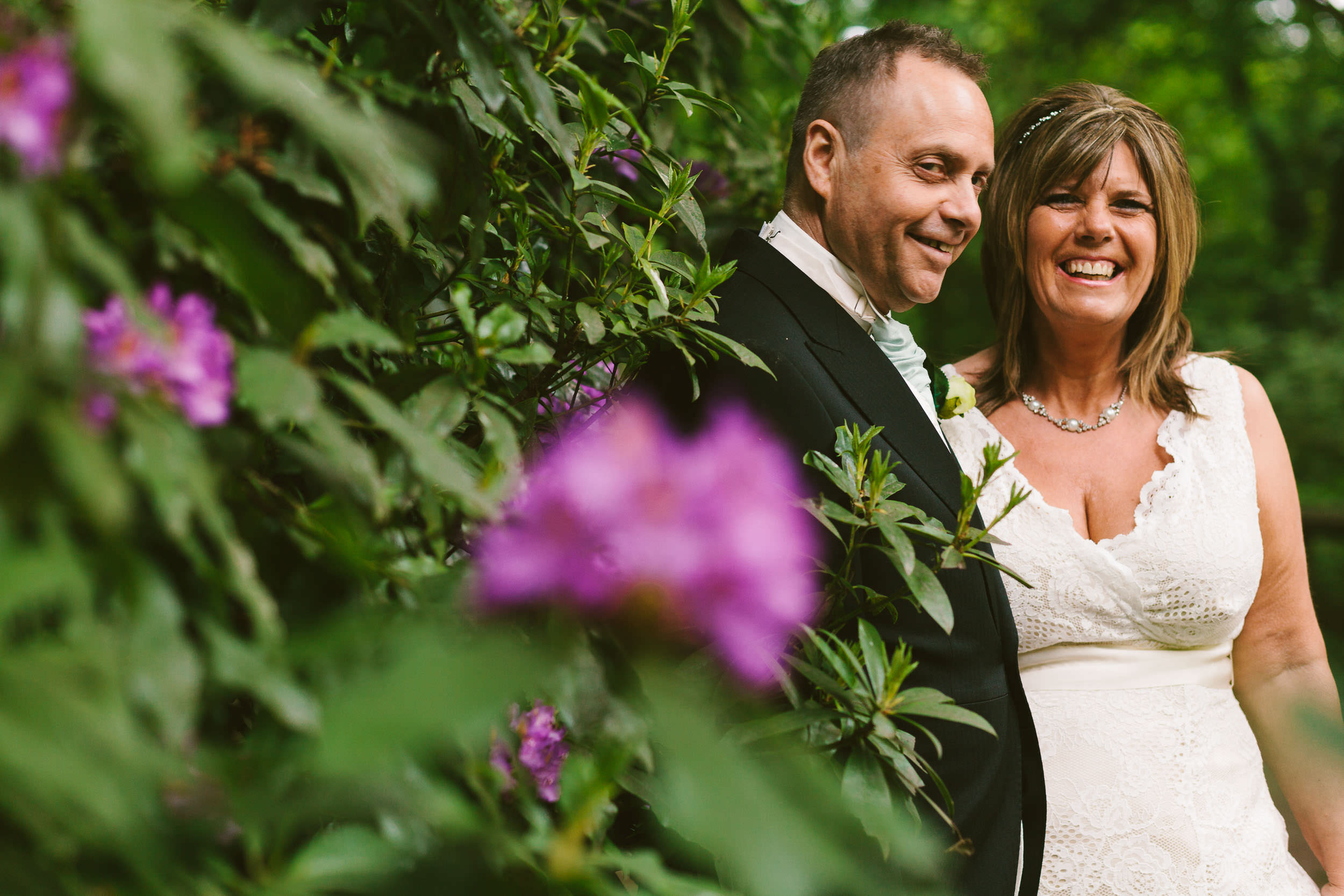 Bride and groom laugh with trees and flowers in foreground