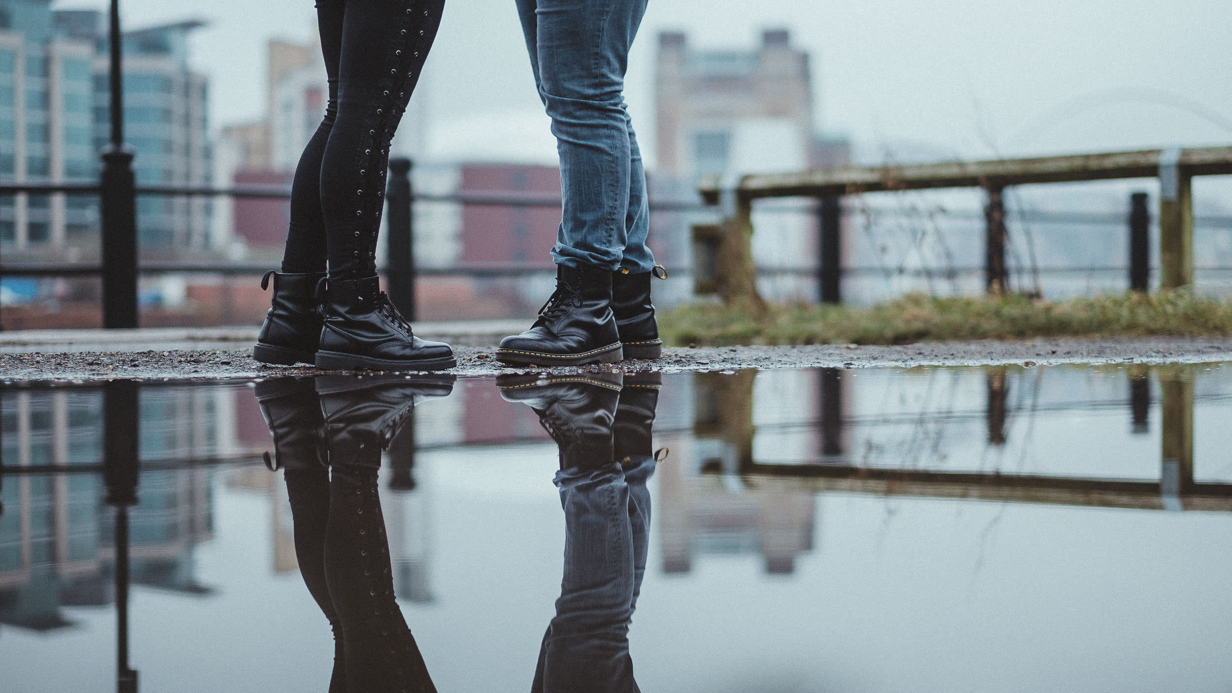 Close up of couples wearing Doc Martin boots reflected in puddle with Baltic Gateshead in background