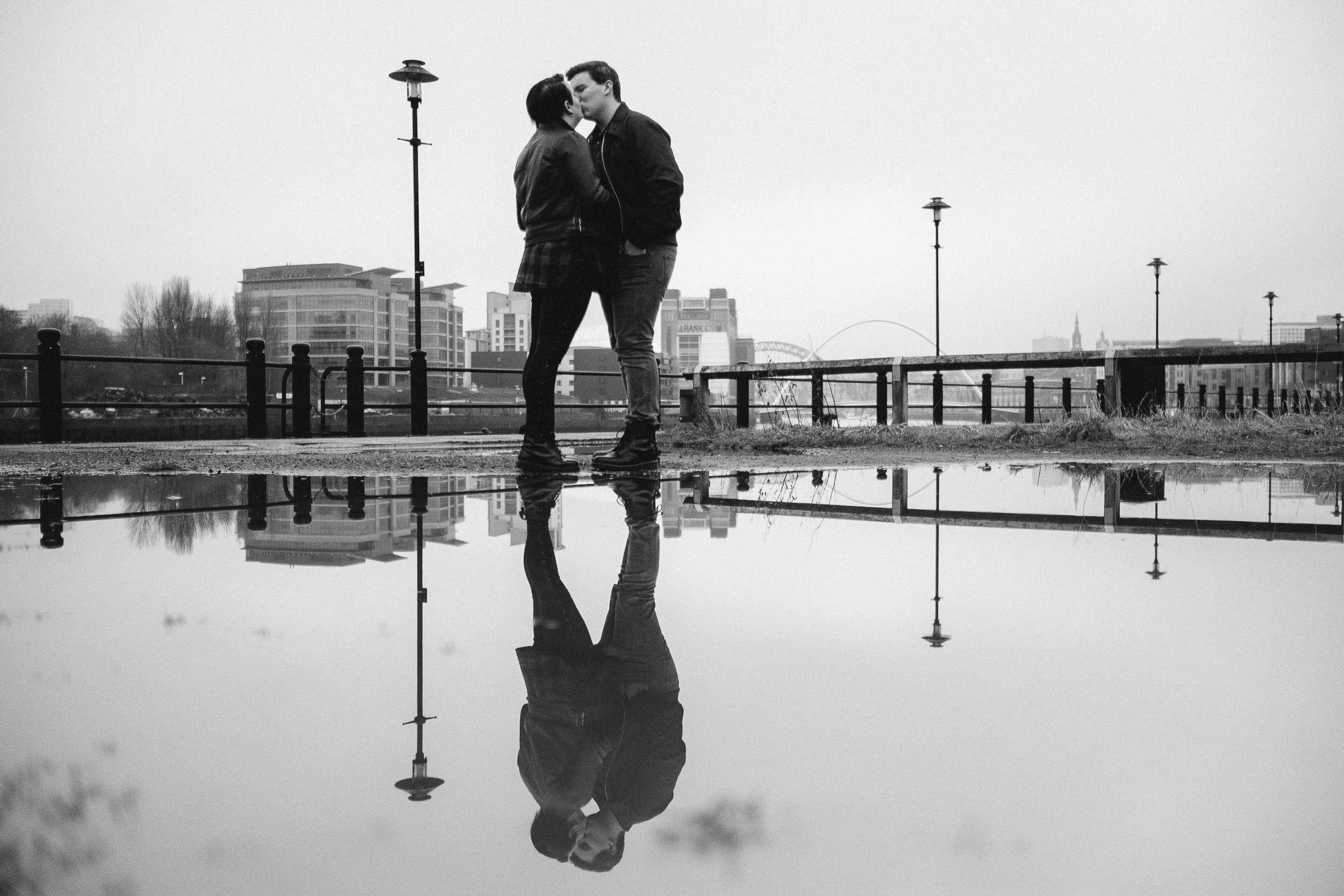 A black and white photo of a couple kissing on Newcastle Quayside with their reflection in a large puddle