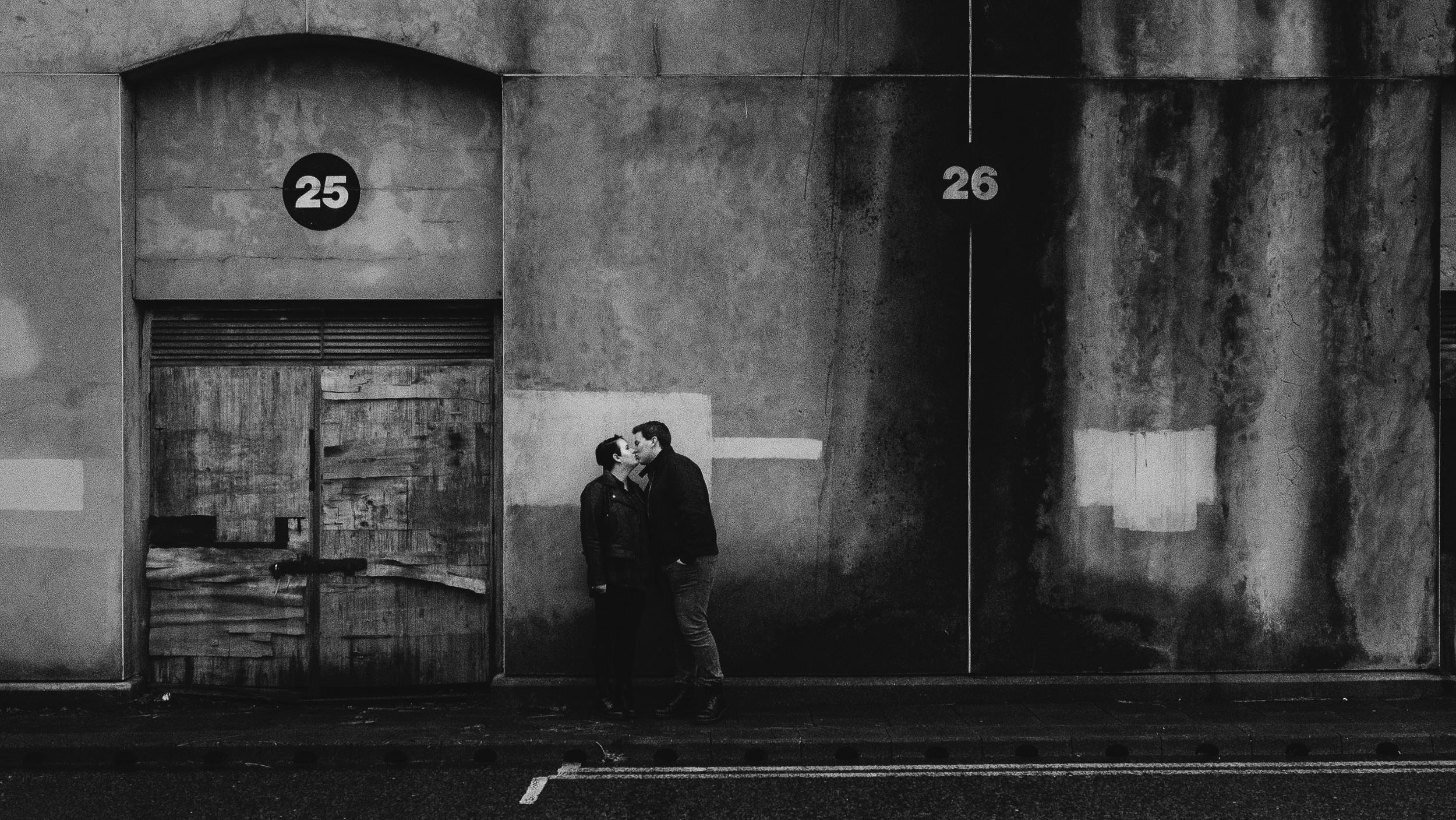 A black and white photo of an engaged couple embracing in front of a wall with peeling paint