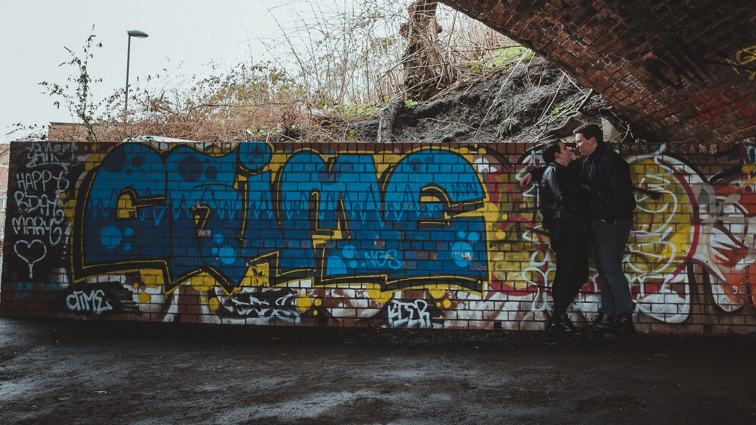 An engaged couple face each other in front of a brick wall covered in graffiti