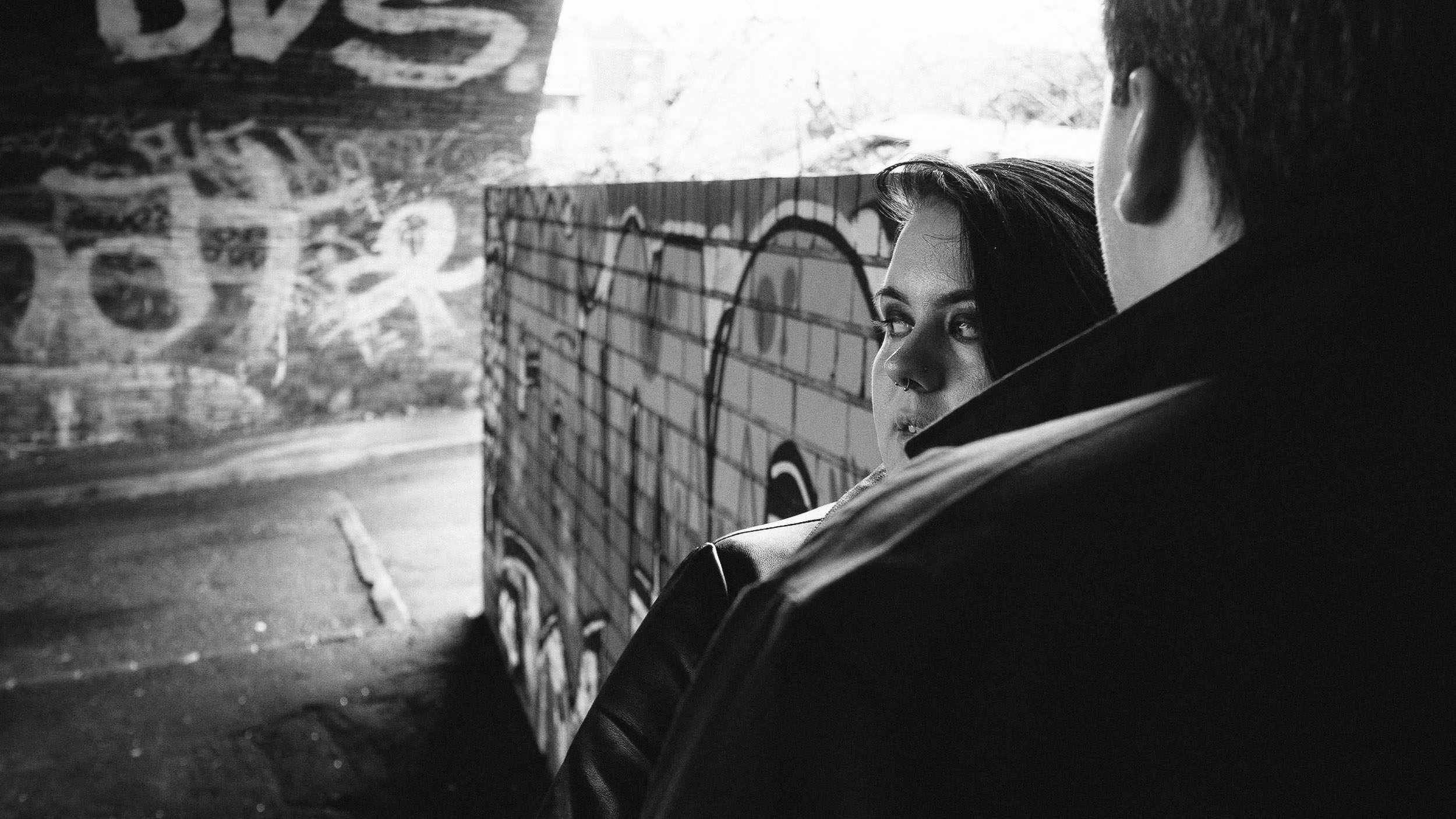 A black and white photo of an engaged couple standing under a brick arch surrounded by graffiti