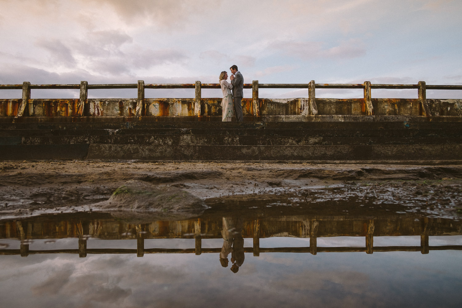 Engaged couple hold hands while standing in ruined and rusty outdoor swimming pool
