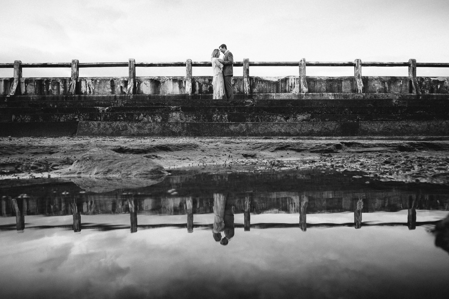 Black and white photo of couple posing in lido at Tynemouth longsands