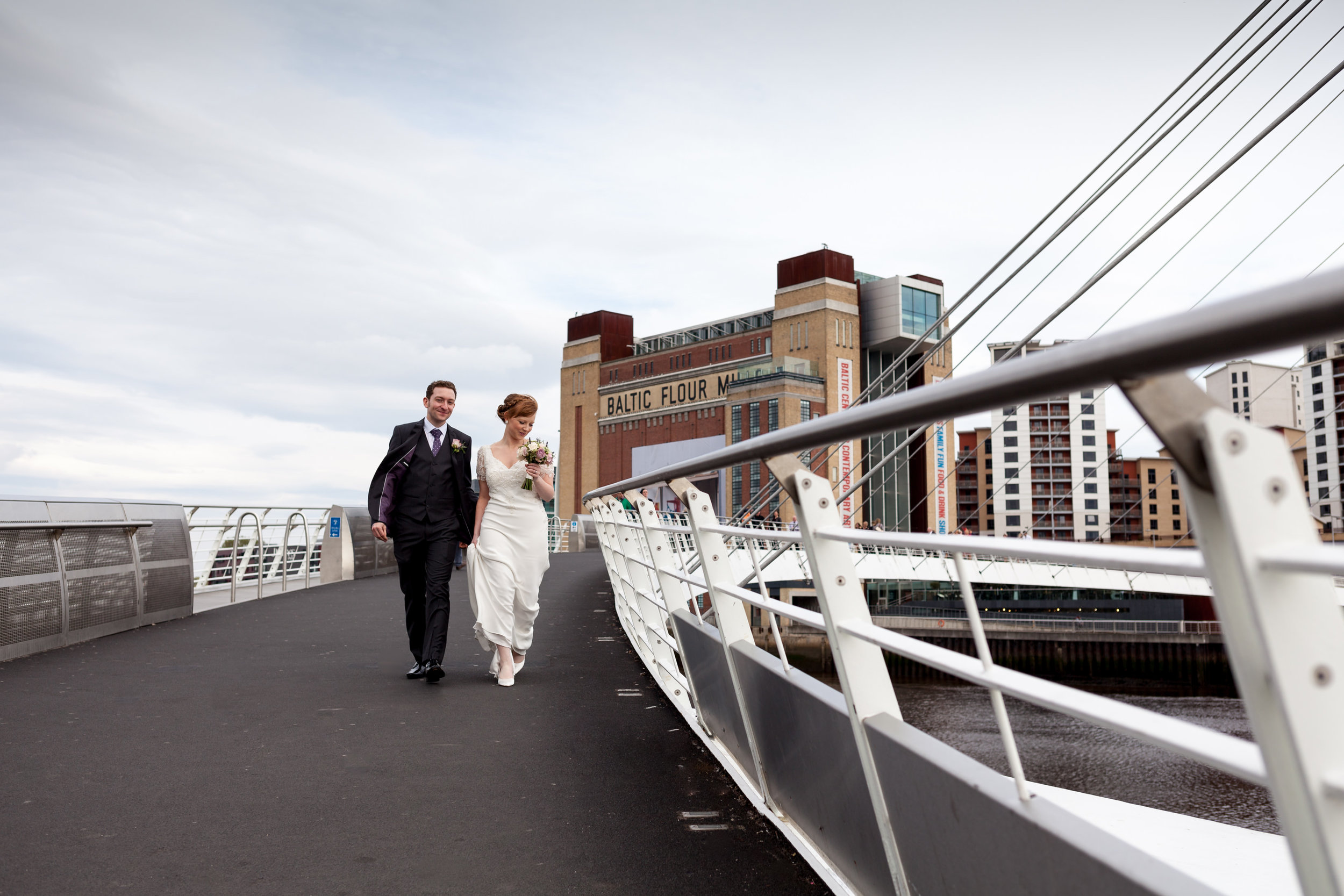 Katy-Rose and Chris walk over the Millennium Bridge on Newcastle Quayside with the Baltic wedding venue in background