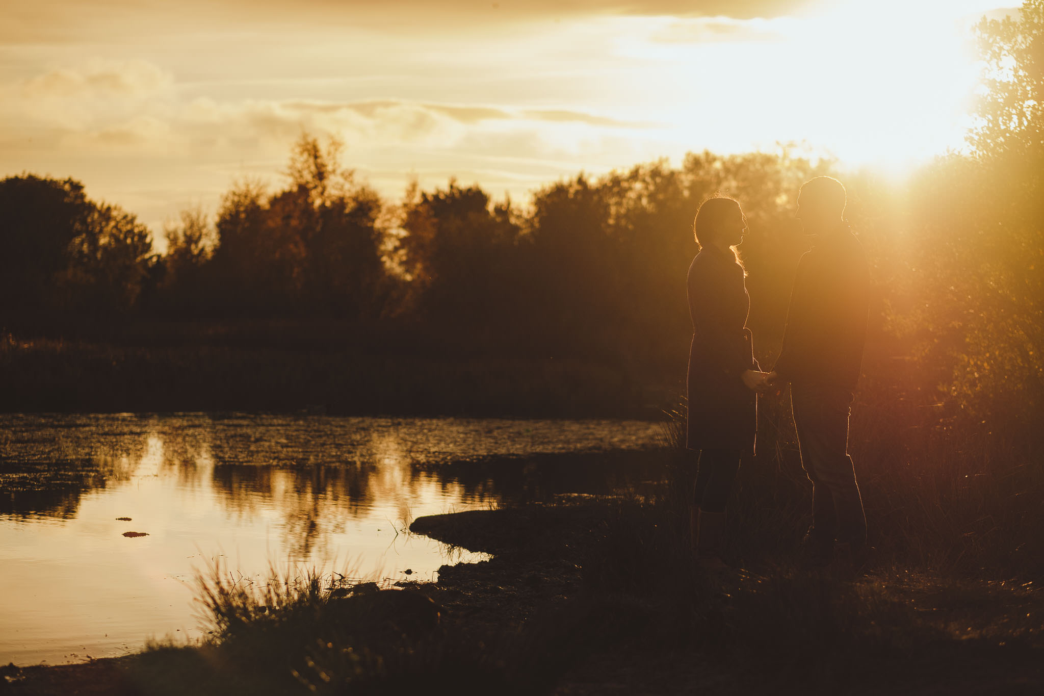 Sun drenched photo of an engaged couple holding hands near a lake