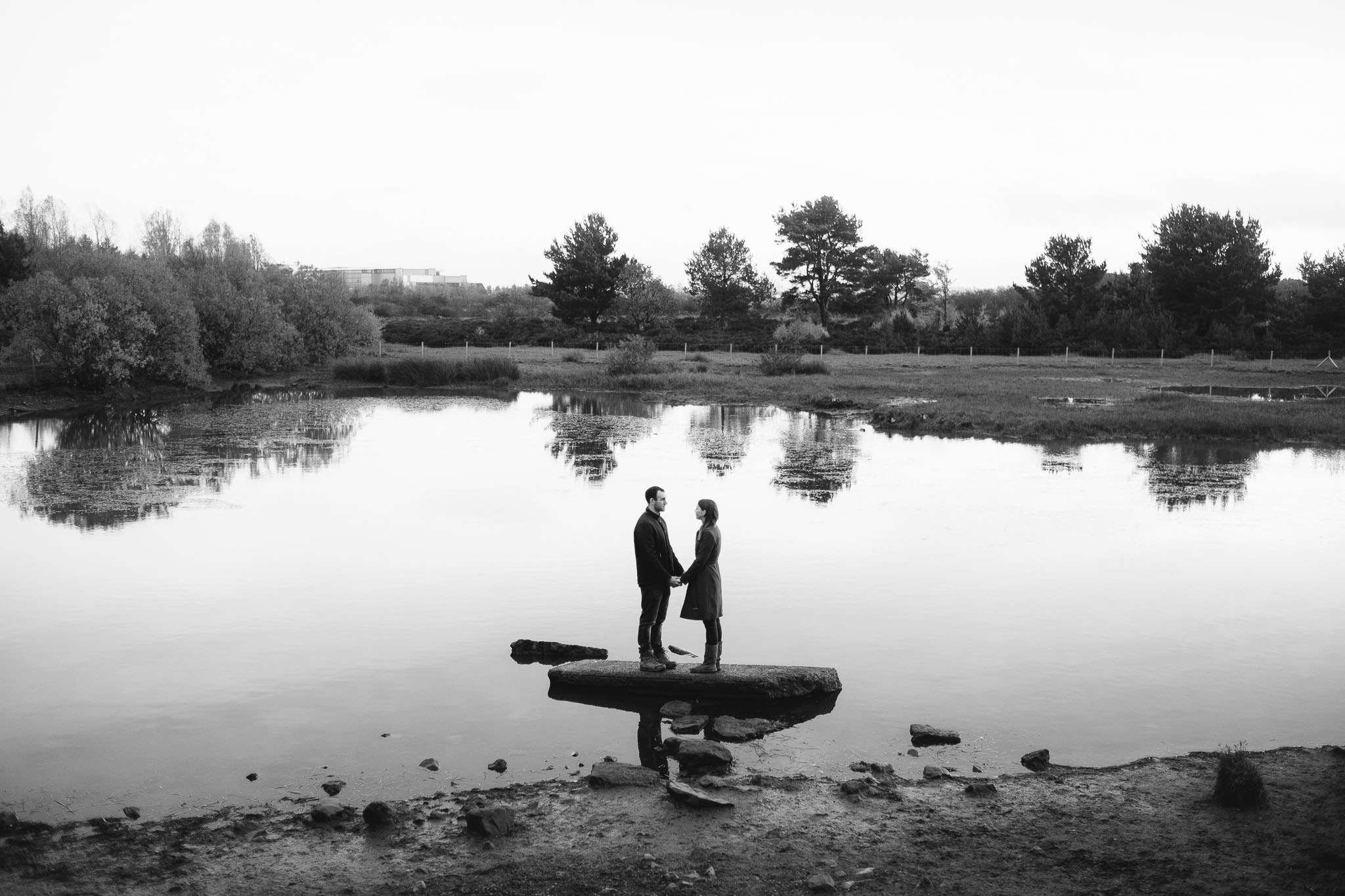 A black and white photo of a couple standing on a rock on a lake in Newcastle