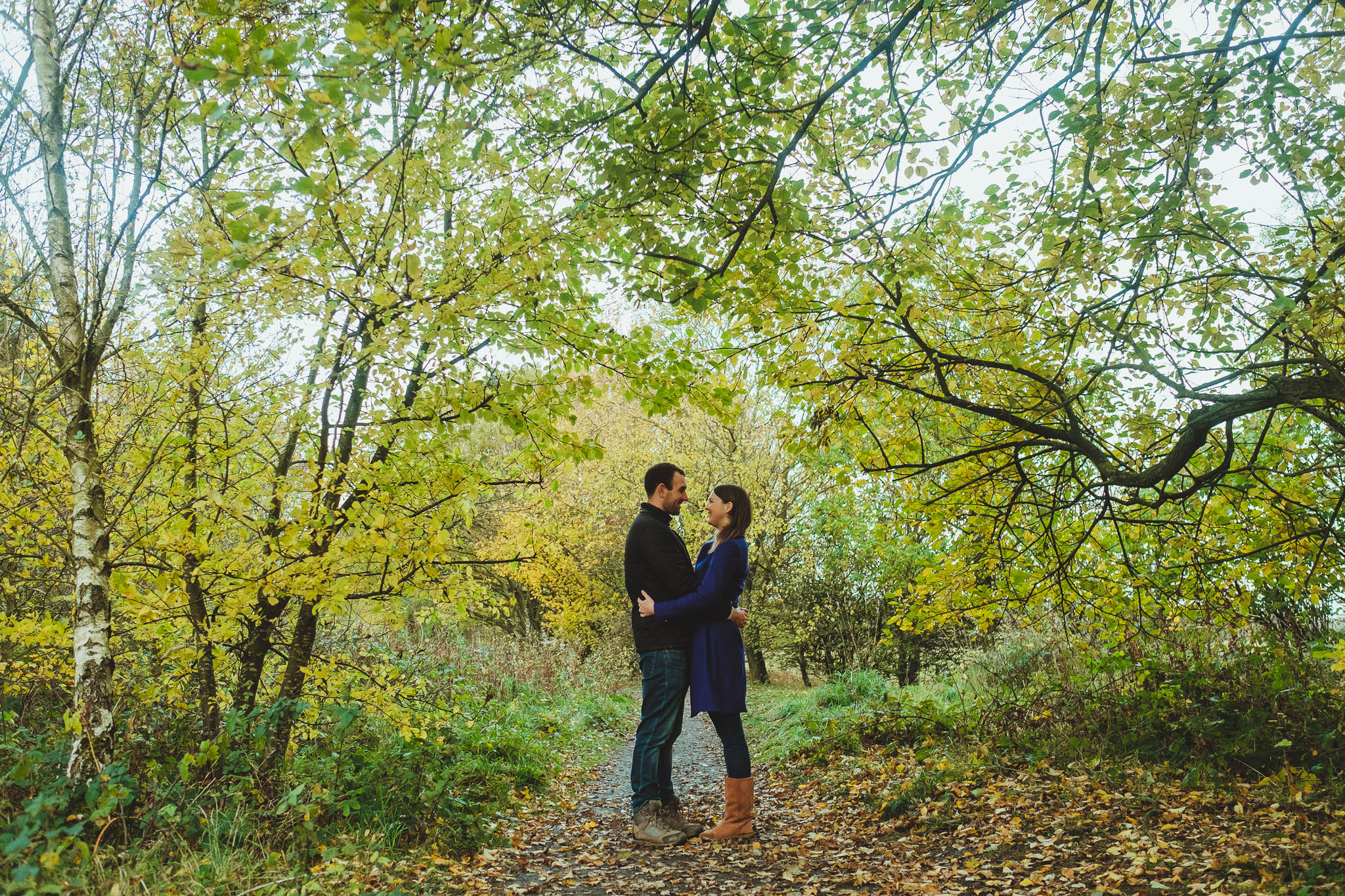 Engaged couple embracing under a canopy of leaves in Newcastle