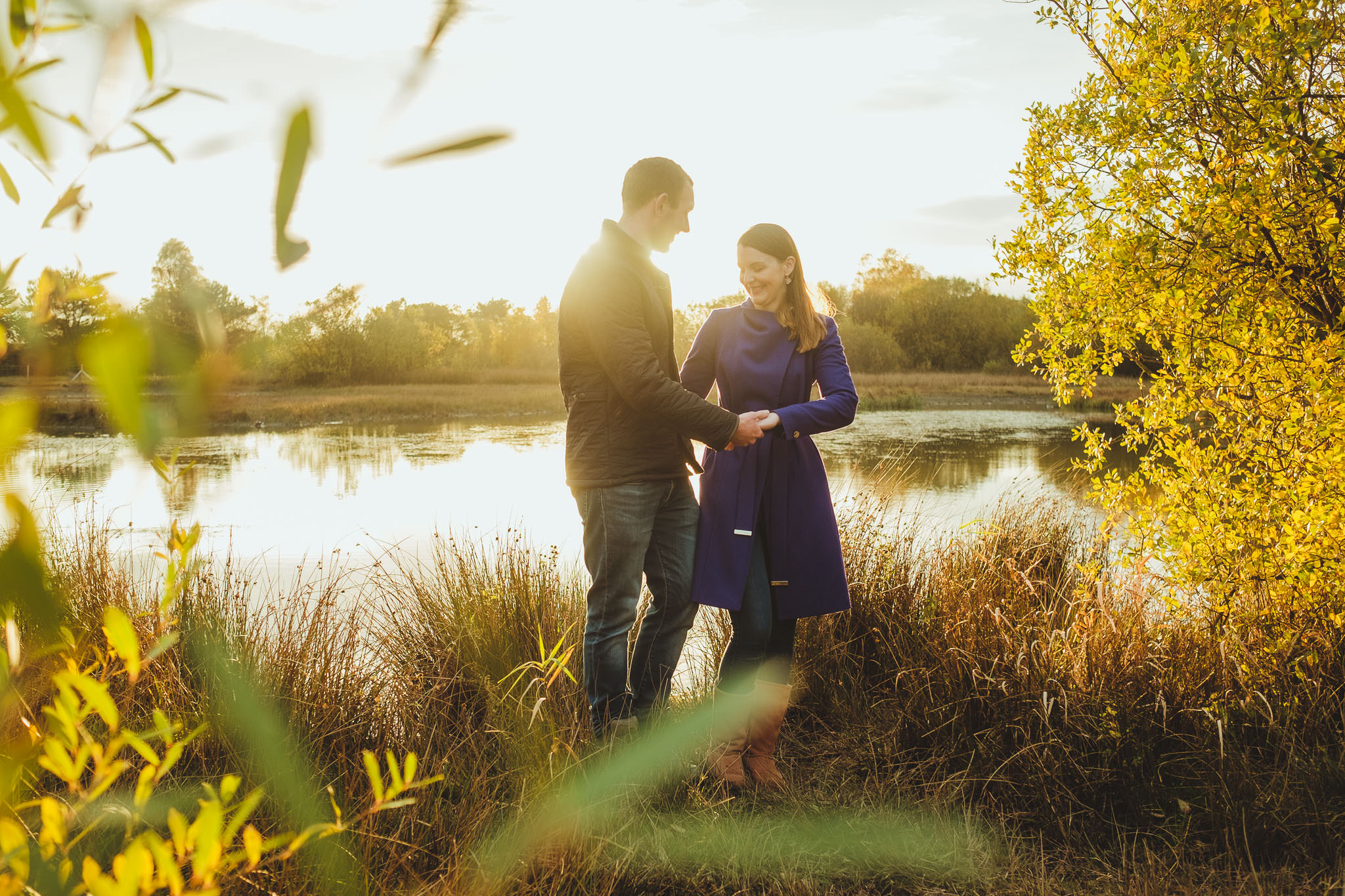 Colourful photograph of a couple laughing and holding hands in a nature reserve in Newcastle