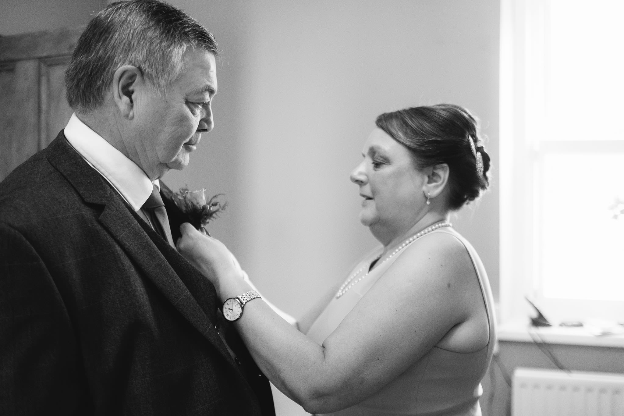 A black and white photo of the bride's mother fixing the bride's dad buttonhole