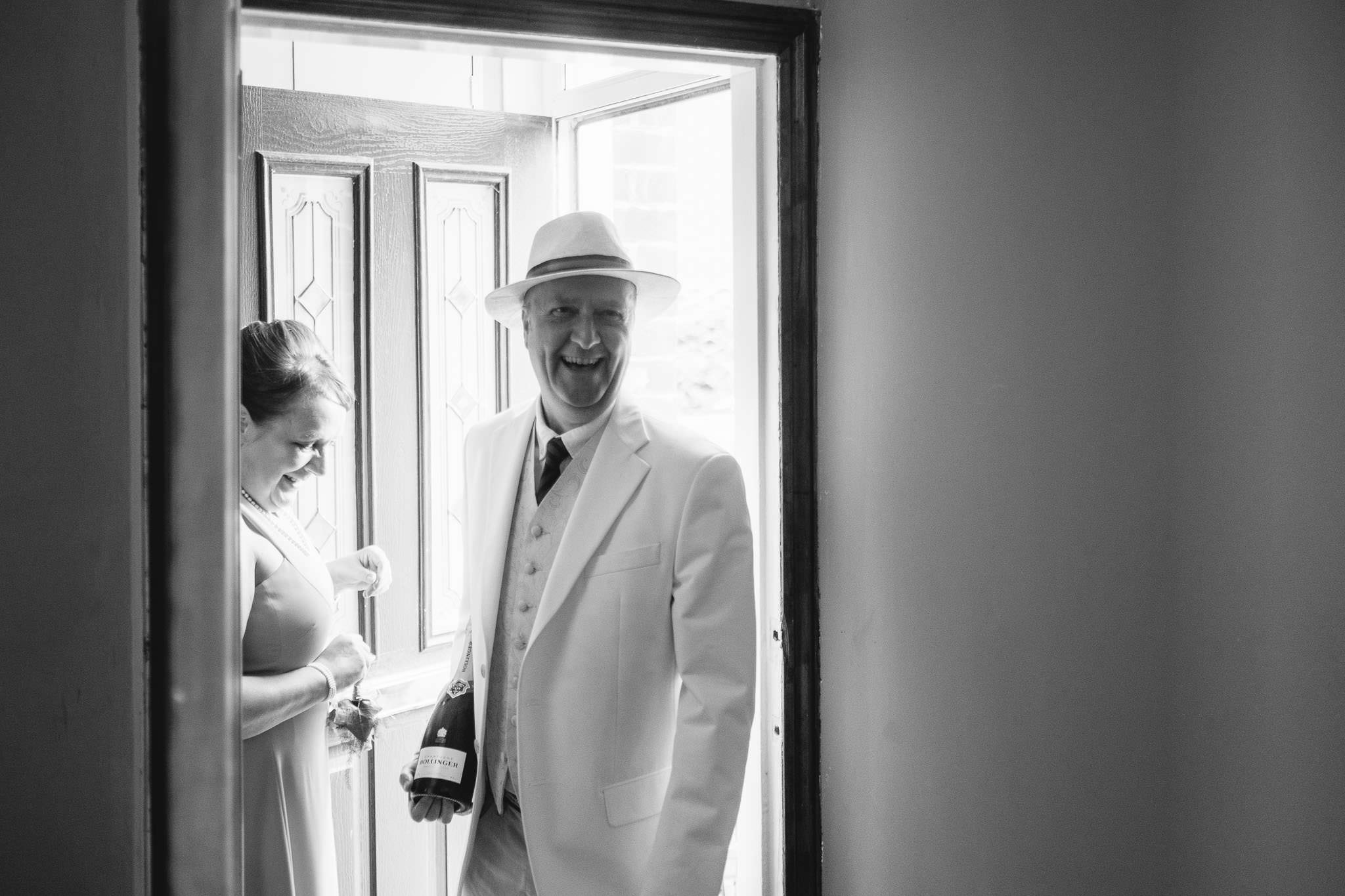 A black and white photo of a guest arriving at the bride's house in Newcastle with champagne