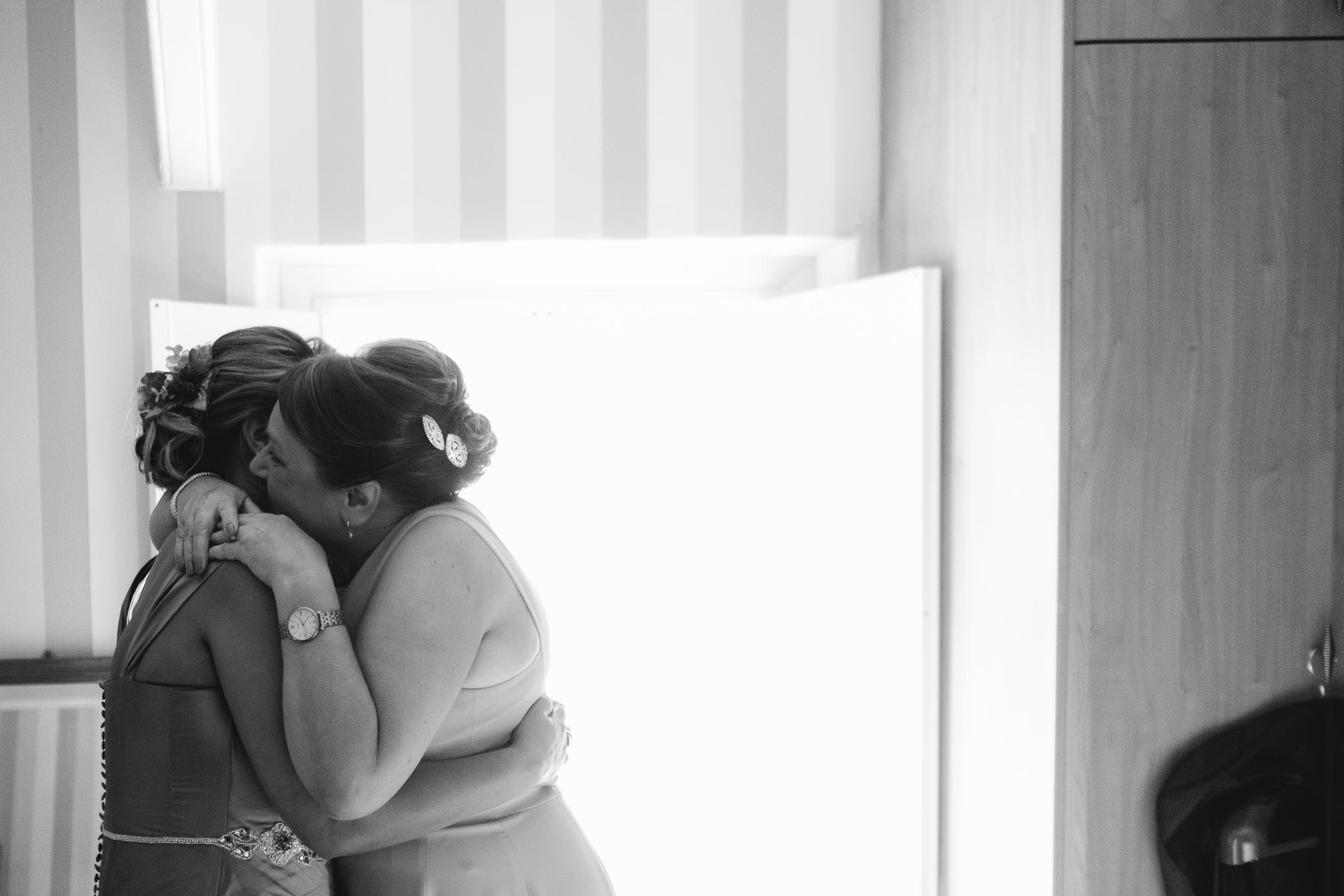 A black and white photo of the bride and her mother hugging before the wedding ceremony