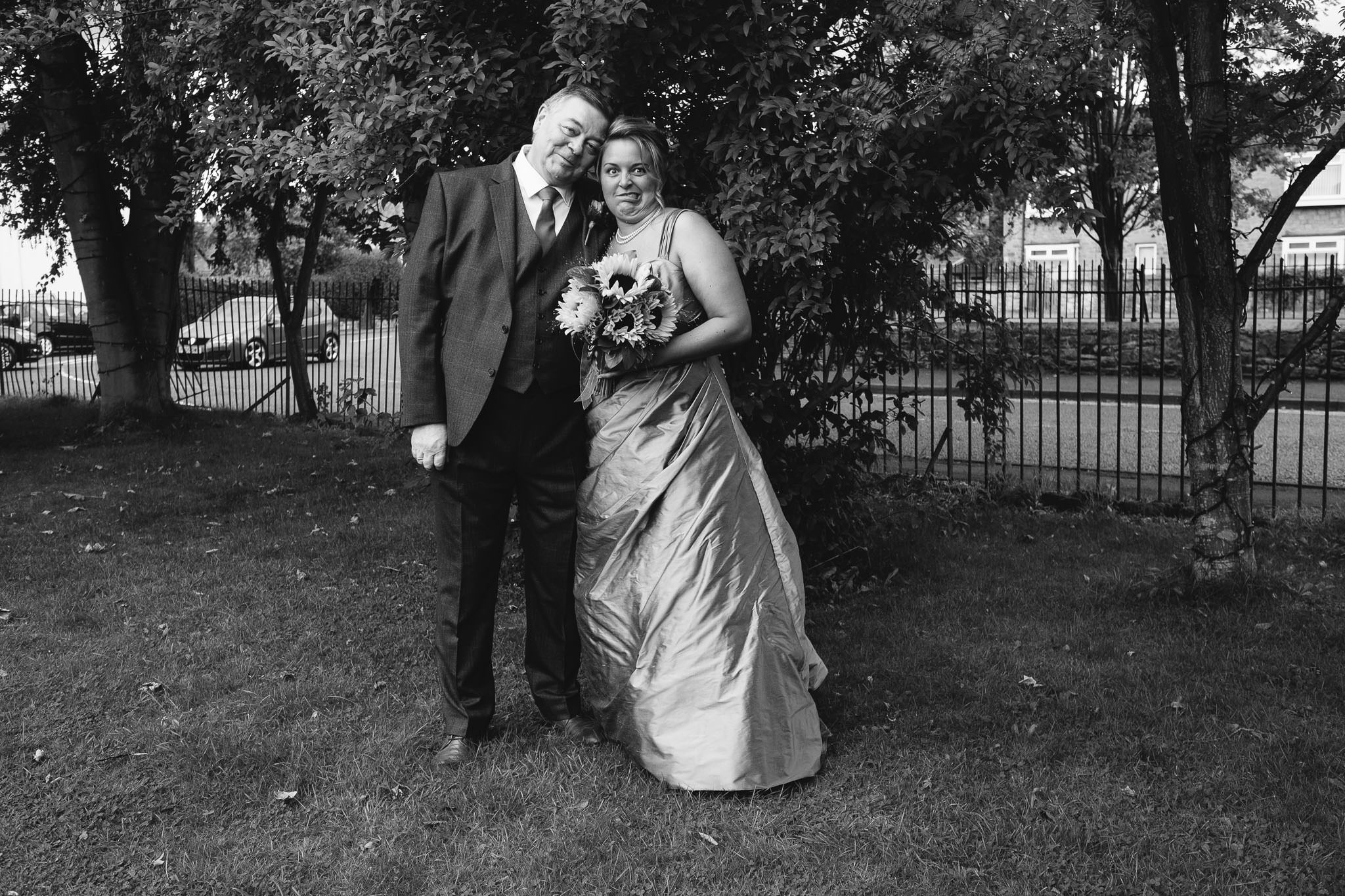 A black and white photo of the bride and her dad pulling funny faces before the wedding