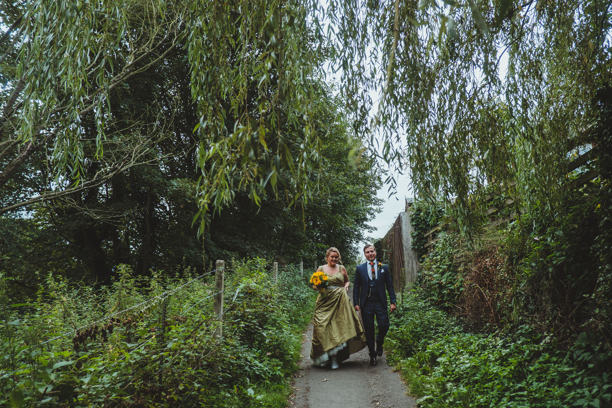 Bride and groom walk through woodland near Newcastle