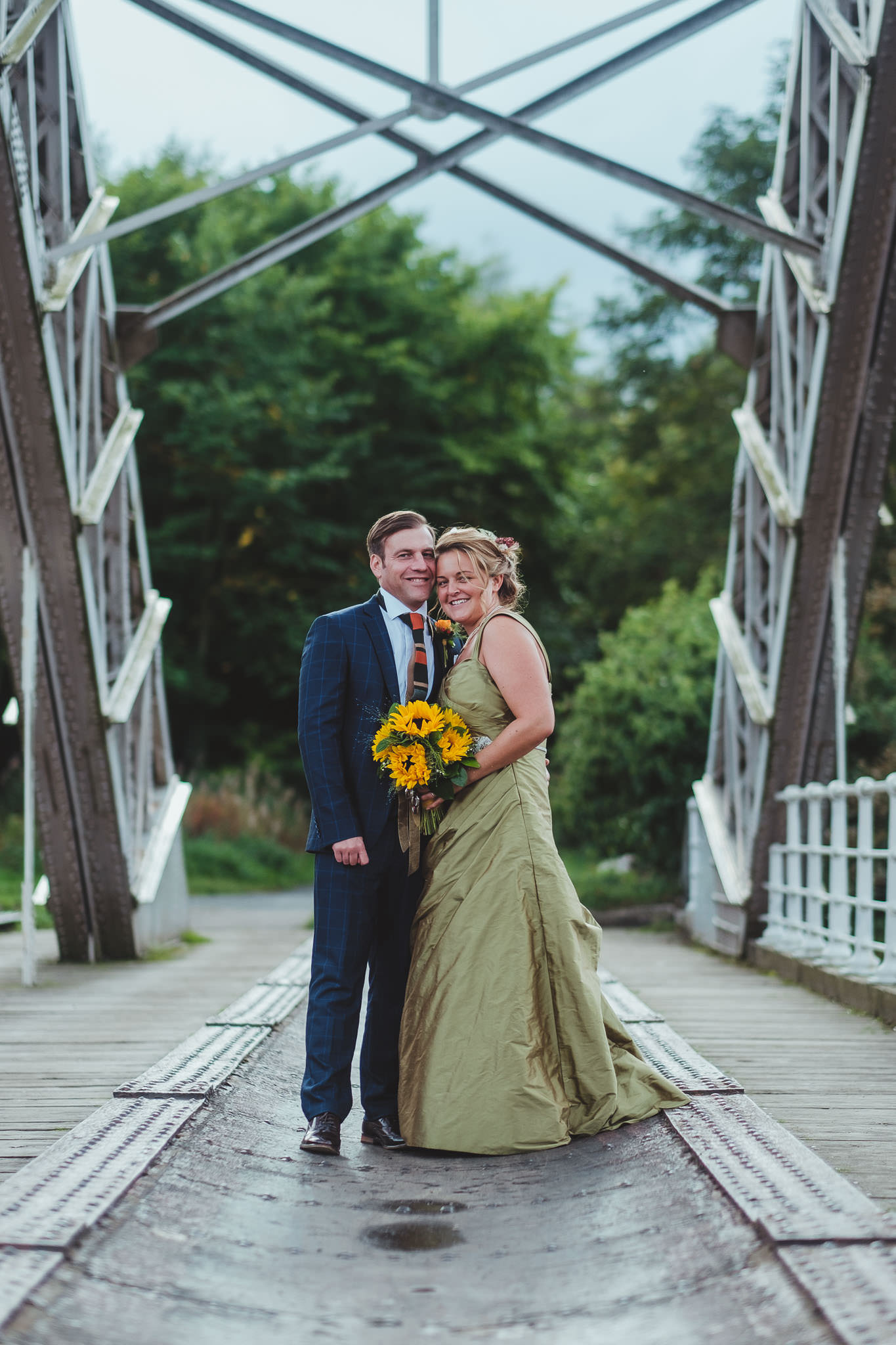 Bride and groom hug on the bridge at Hagg Bank