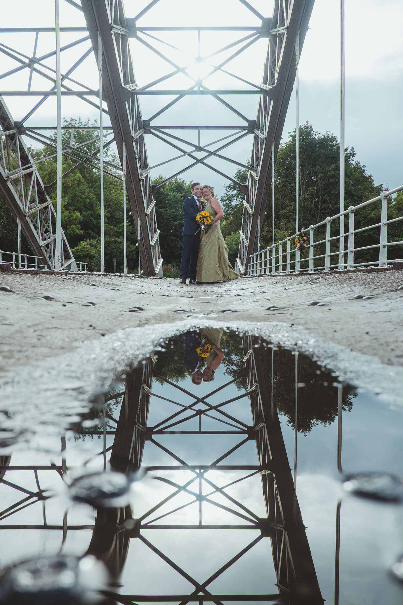 Bride and groom reflected in a puddle on a bridge