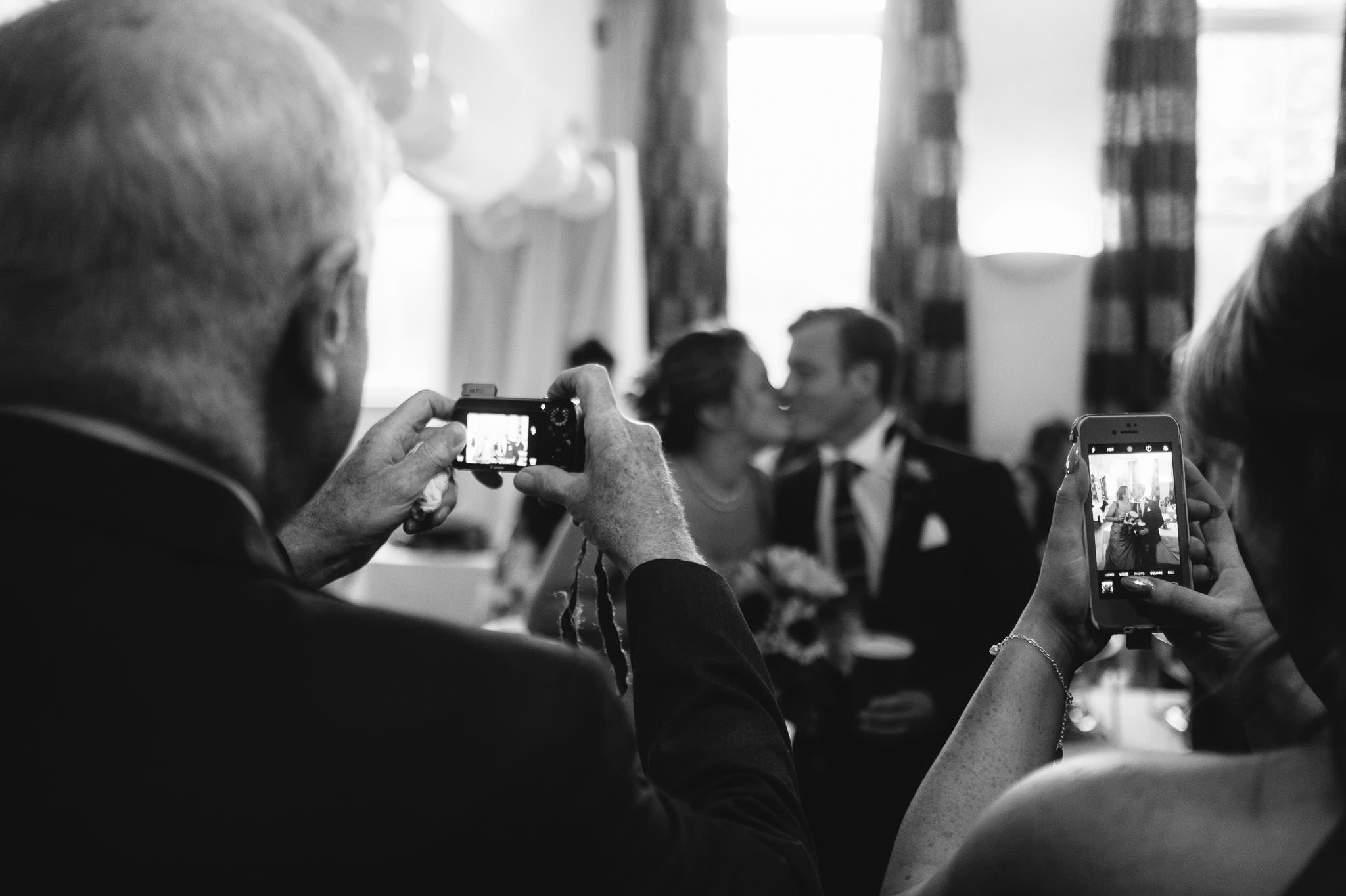 A black and white photo of guests photographing the bride and groom kissing