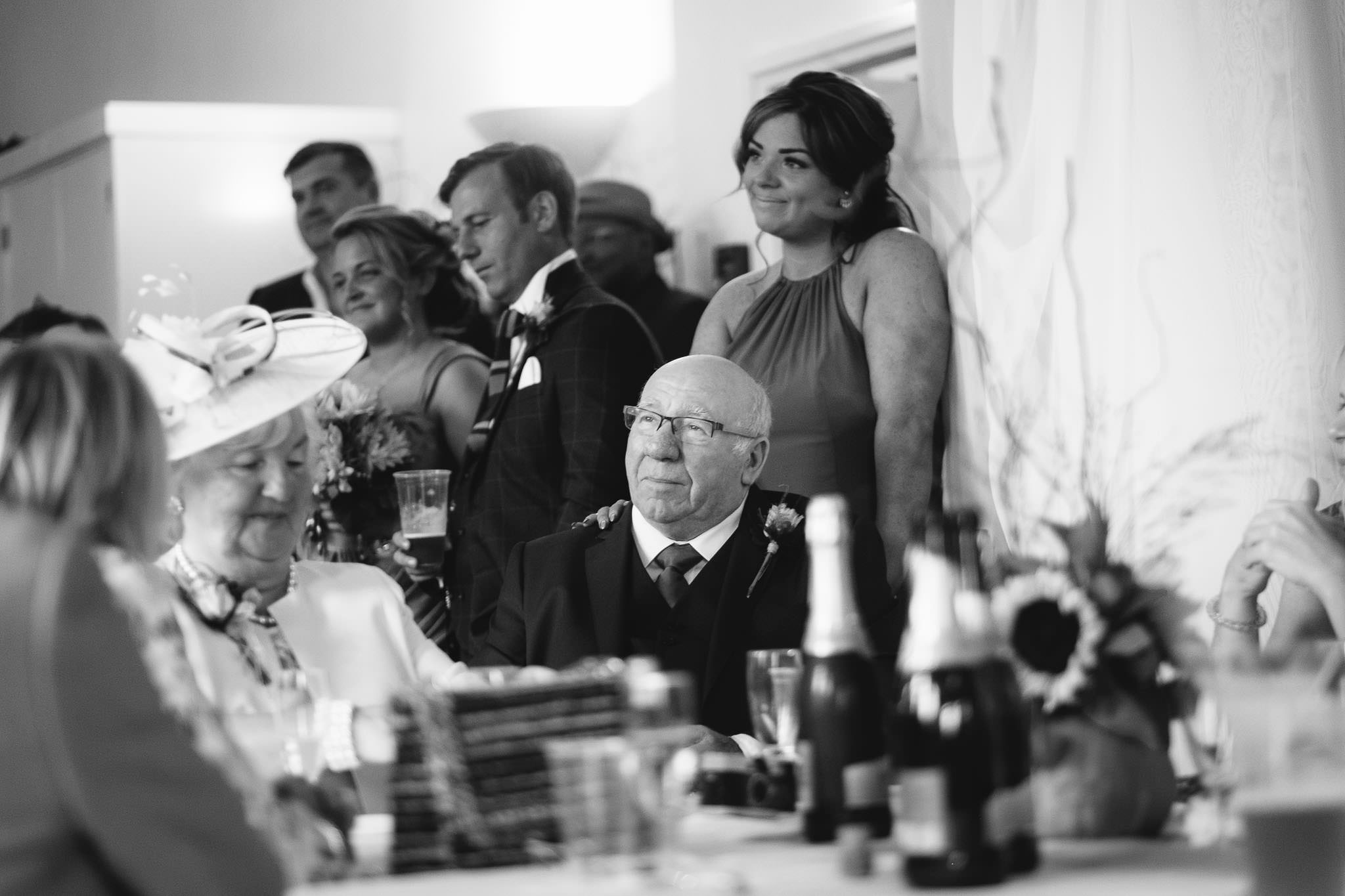 A black and white photo of father of the groom listening to wedding speech, his daughter with her hand on his shoulder