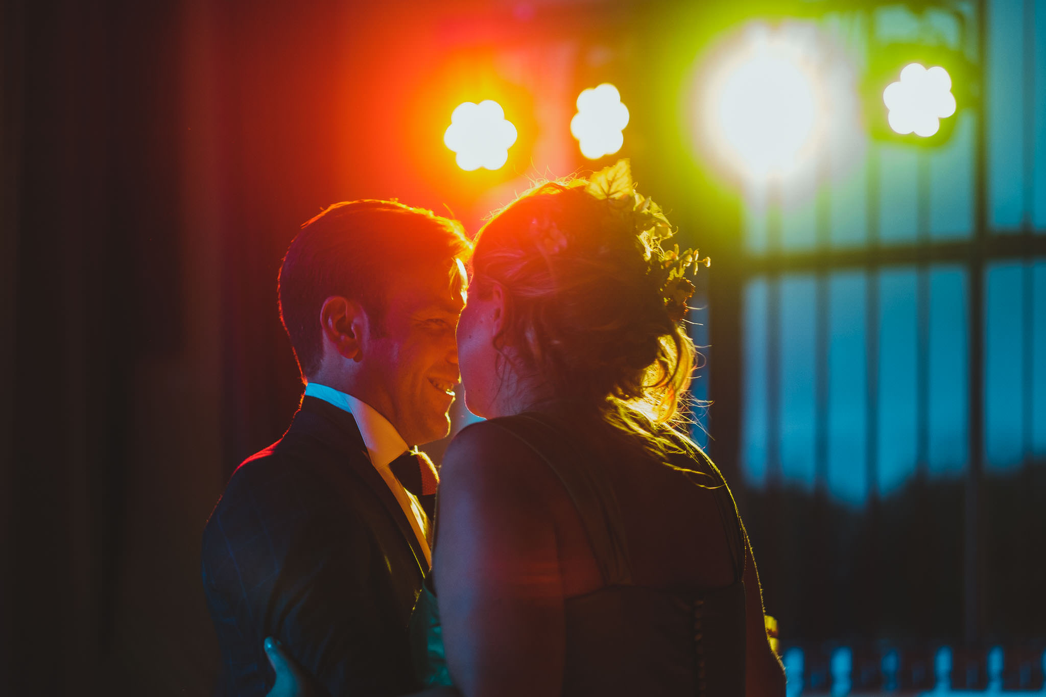 close up of bride and groom first dance lit by disco lights