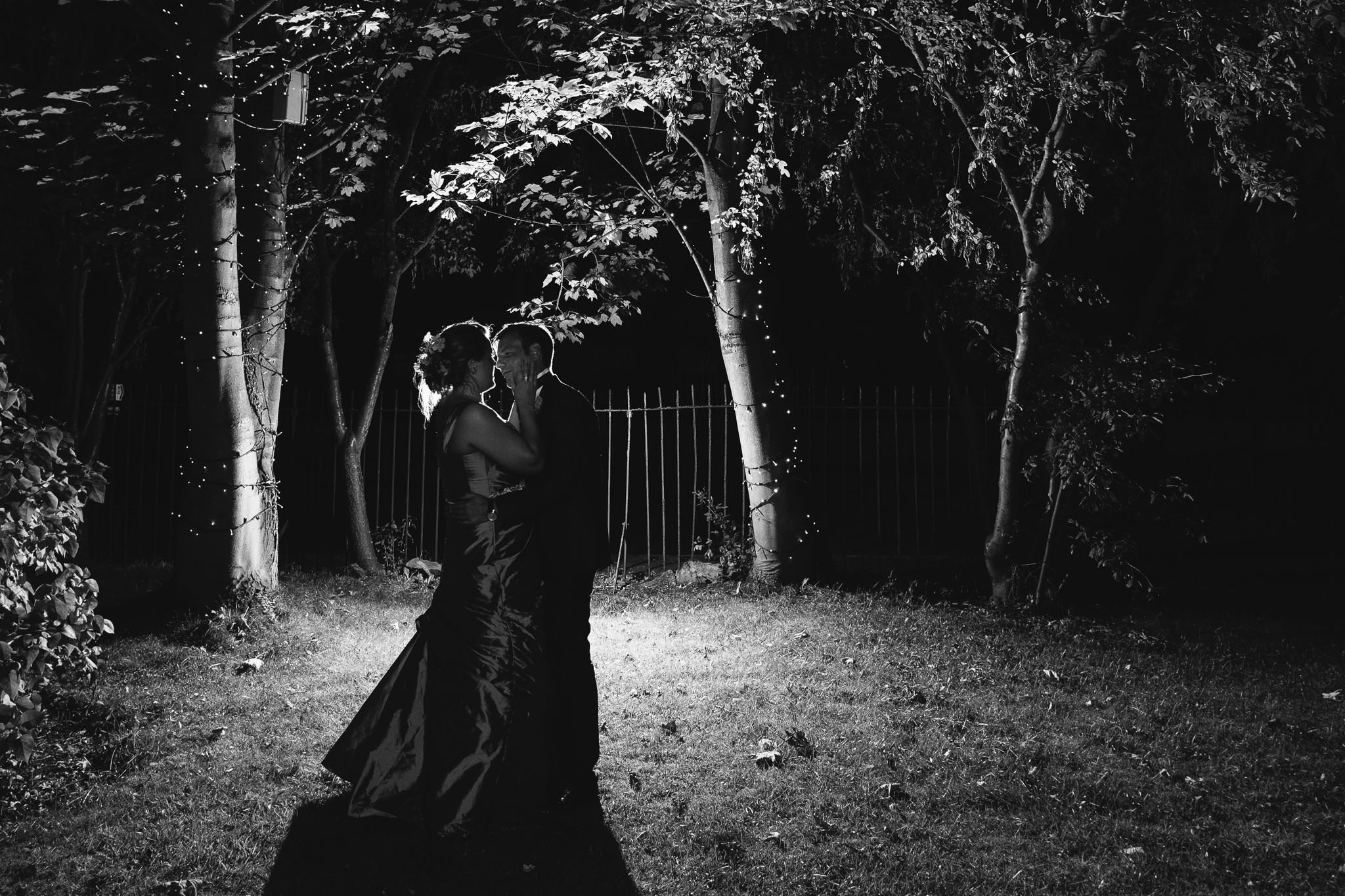 A romantic black and white photo of the bride and groom embracing in the grounds of Wylam Institute at night