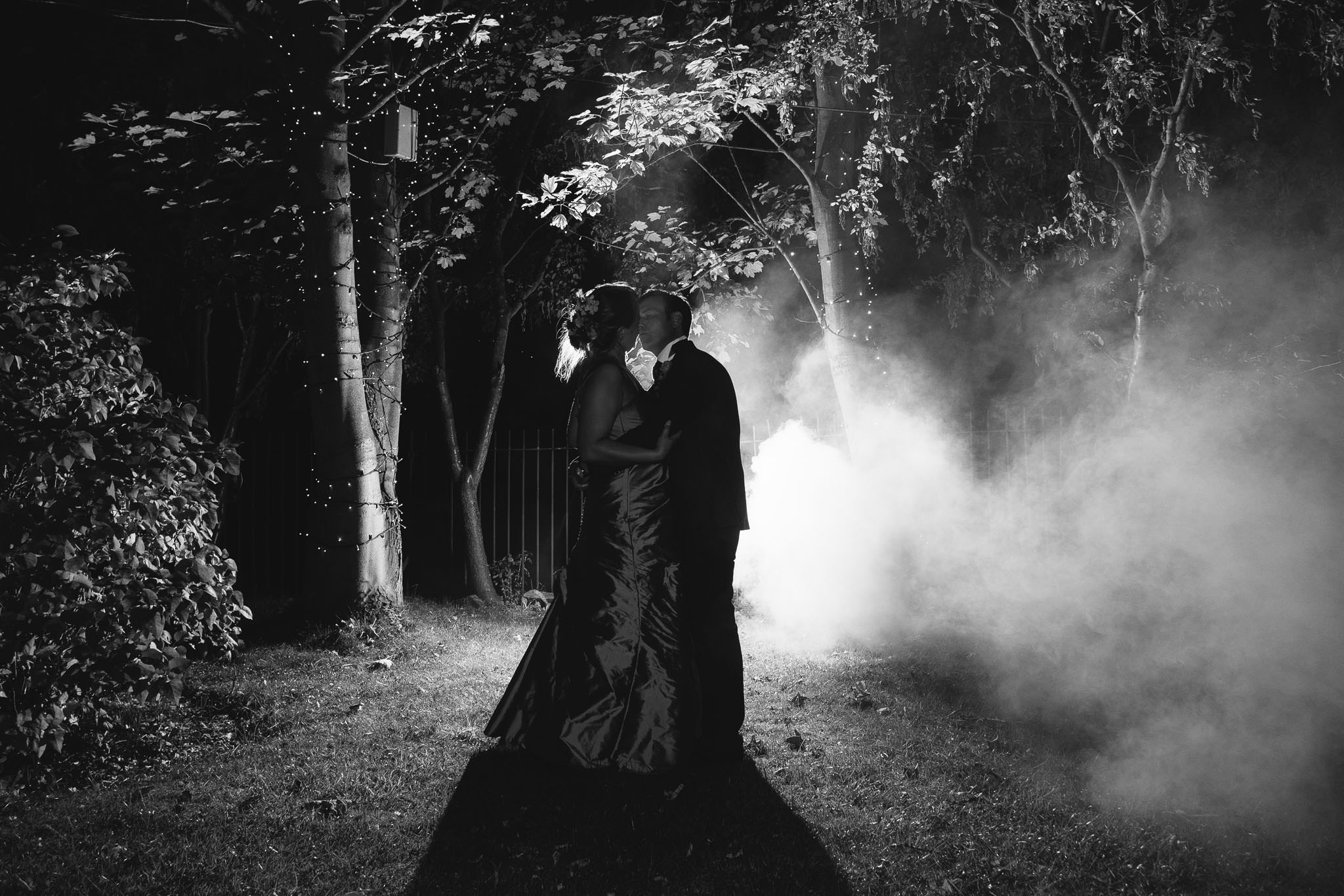 A black and white photo of the bride and groom lit by flash with smoke encircling them