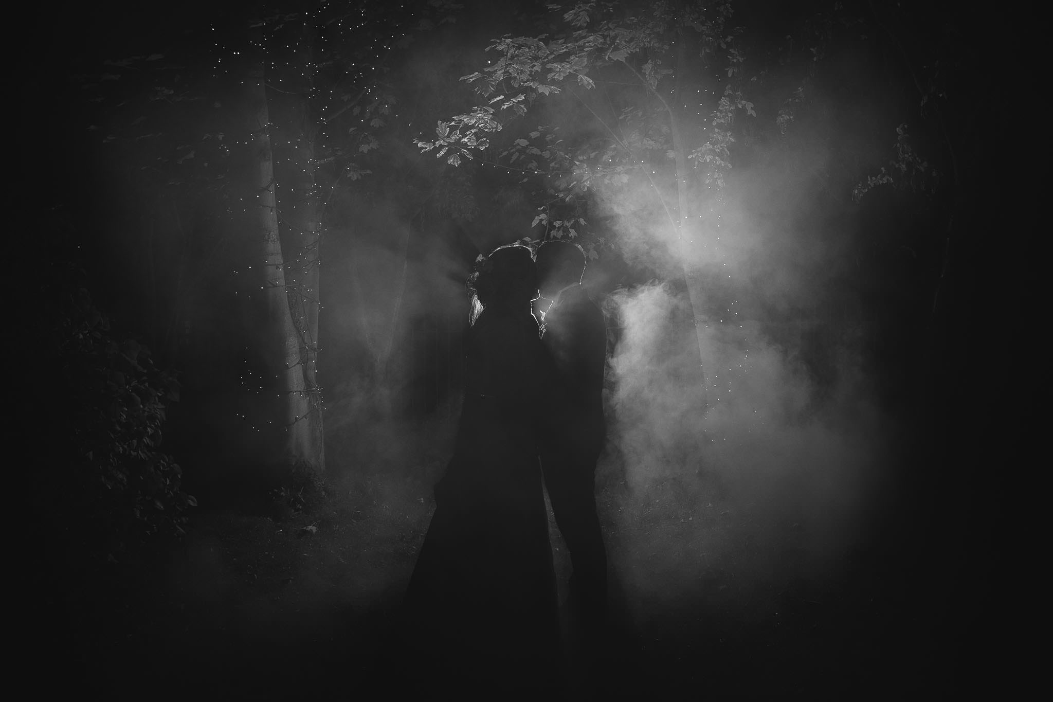 A romantic black and white photo of the bride and groom lit from behind through smoke
